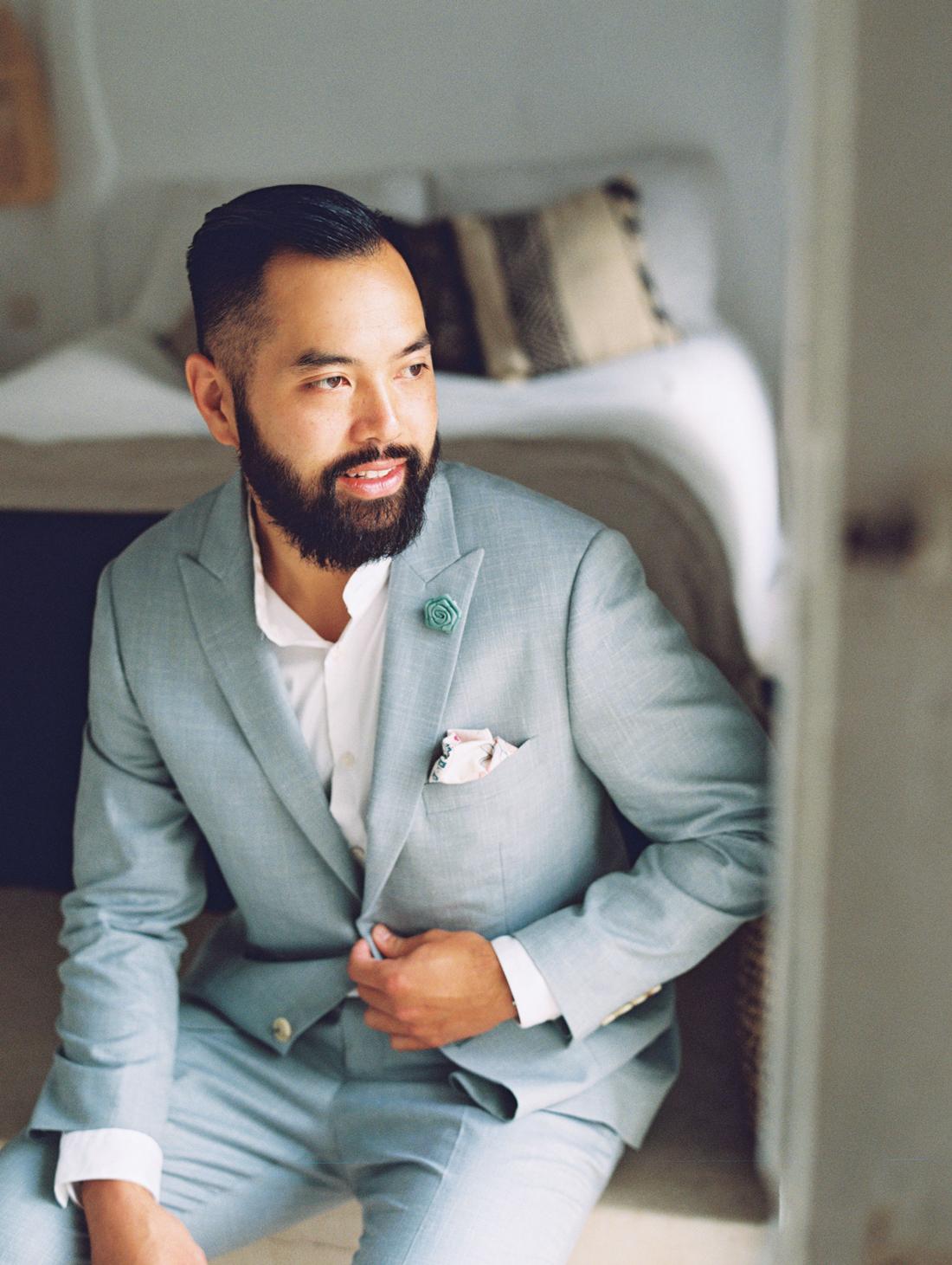 groom sitting wearing sage colored wedding suit