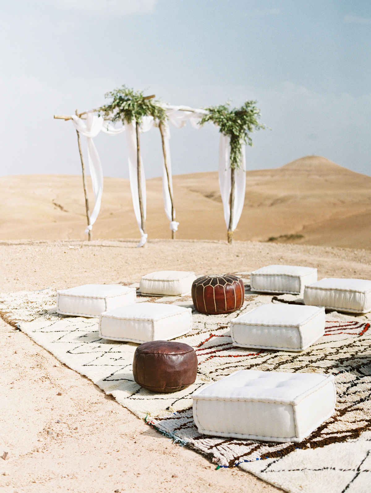 desert wedding ceremony with padded benches on large carpets