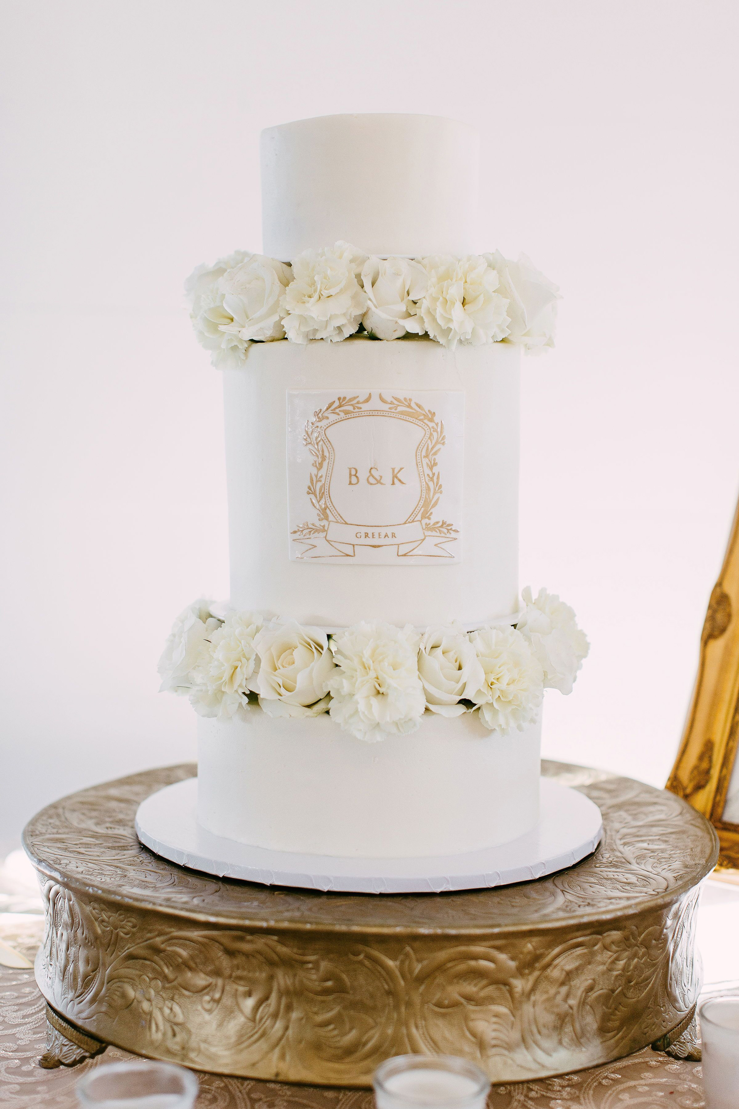 white monogrammed wedding cake with roses