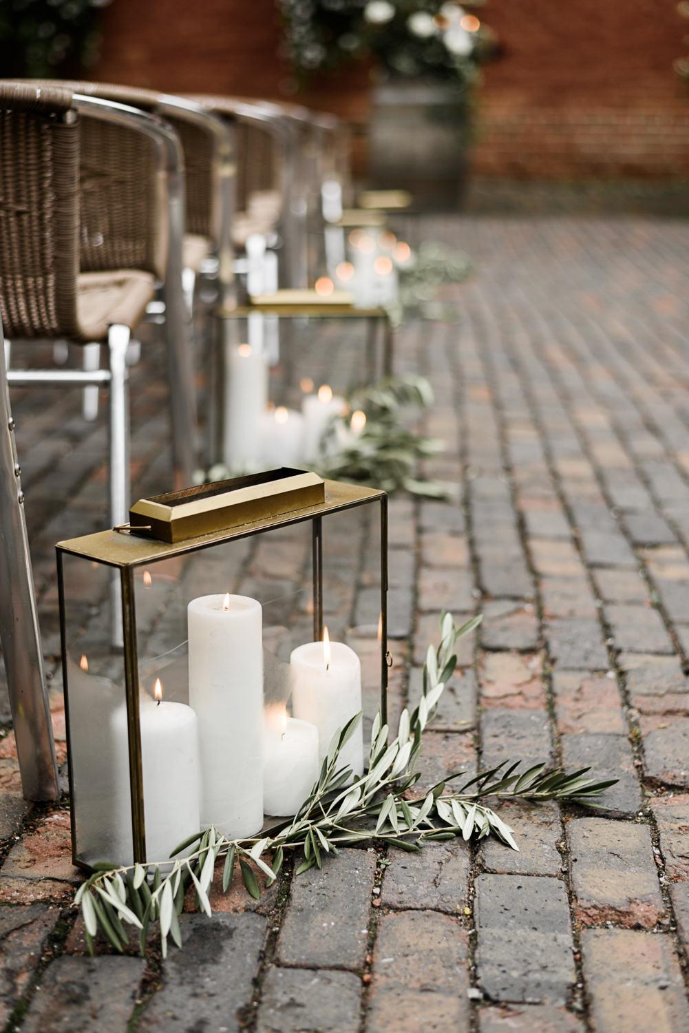 white candles in gold glass lanterns accented with olive branch garland