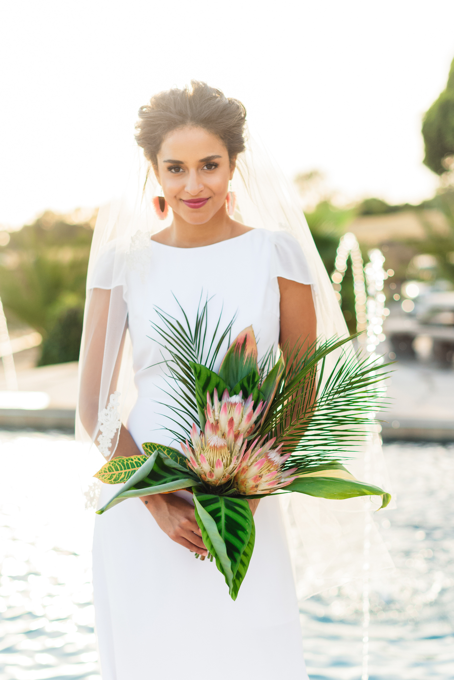 bride holding tropical leaf wedding bouquet