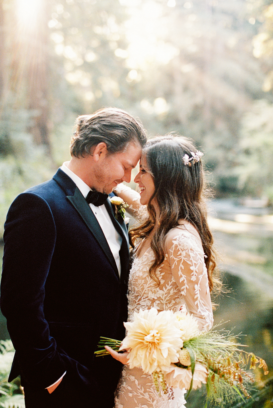 bride and groom facing each other in forest