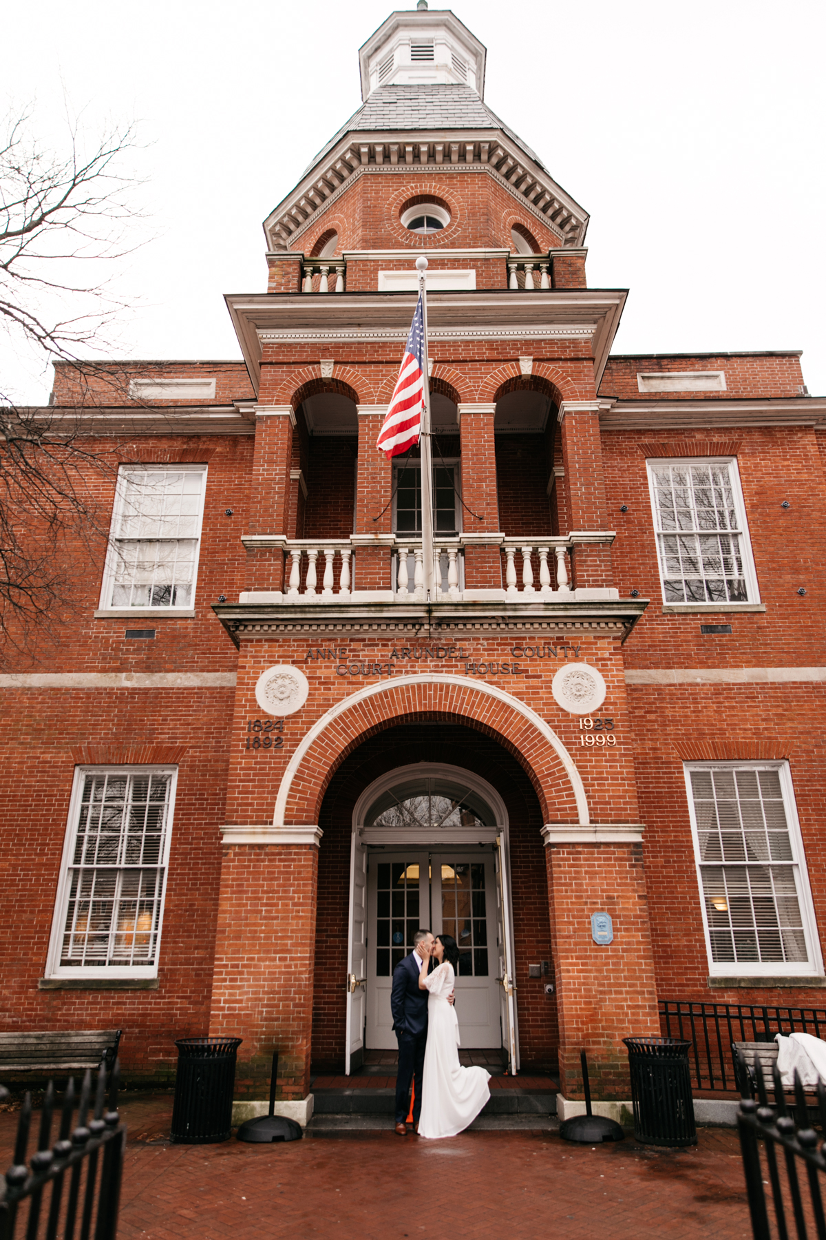 city hall wedding bride and groom kissing in front of red brick building