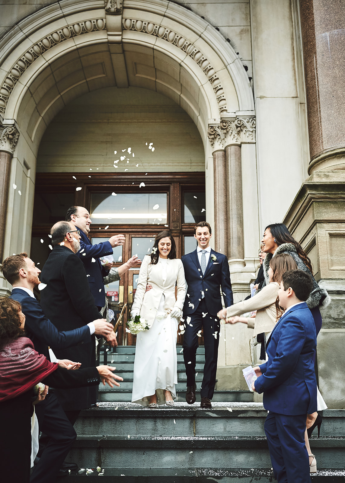 city hall wedding guests throwing flower petals at bride and groom descending staircase