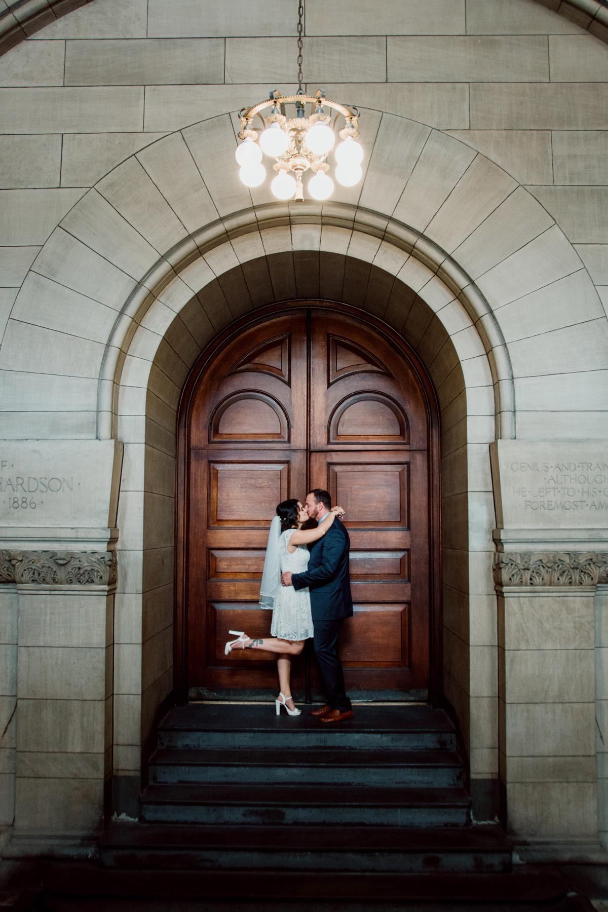 city hall wedding bride and groom kissing in front of wooden door