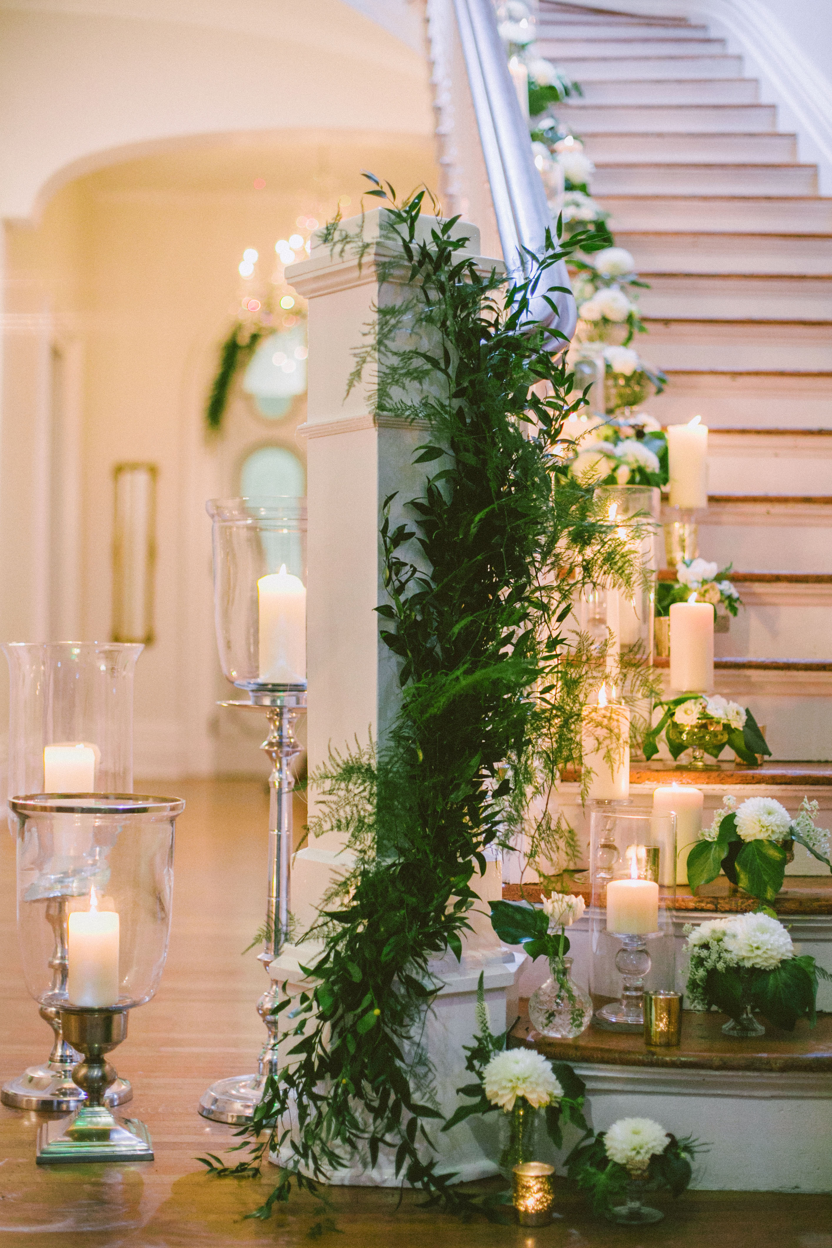 stair banister decor cascading candles and loose greenery