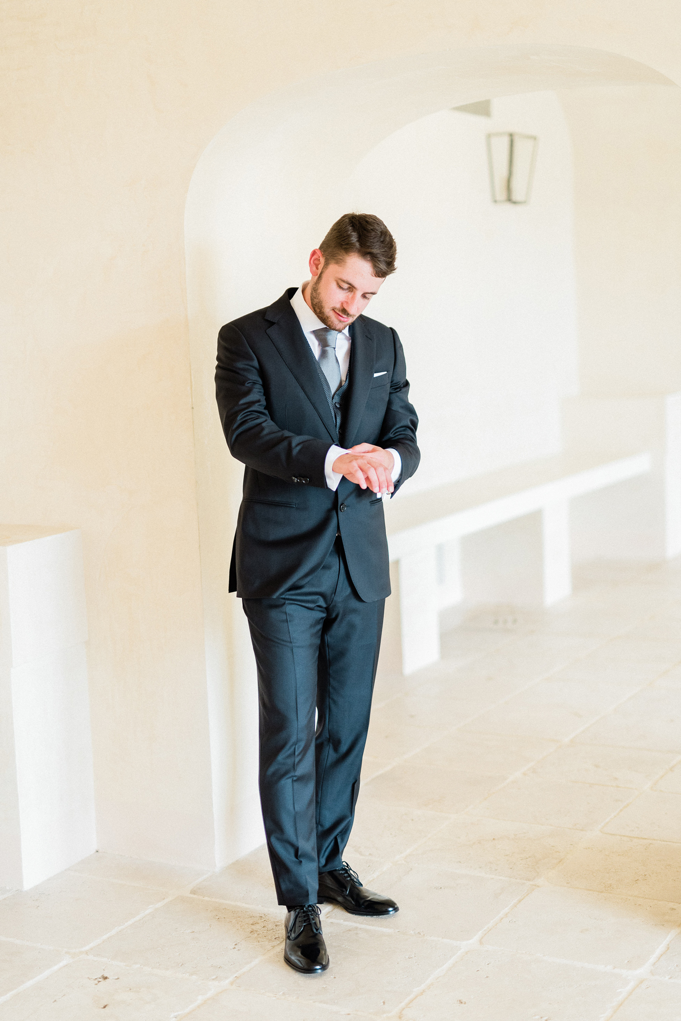 groom wearing dark blue wedding suit and black dress shoes