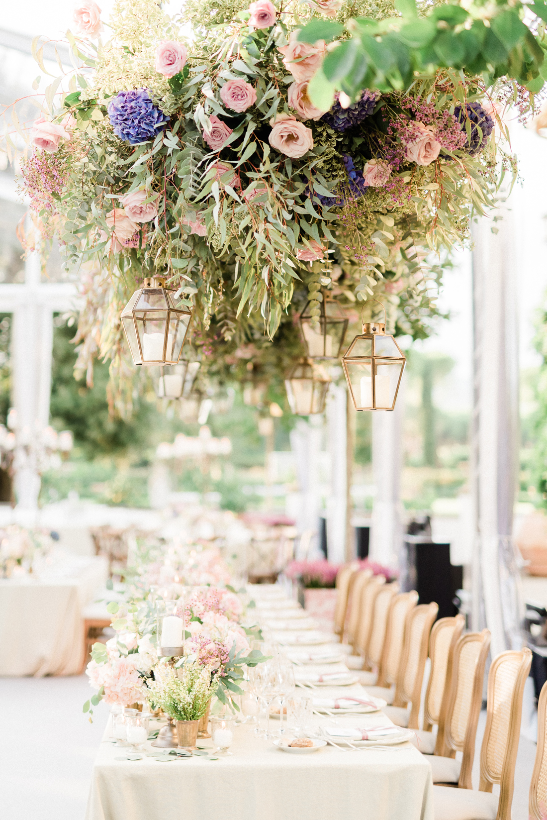 hanging floral decor over long white linen cover reception tables