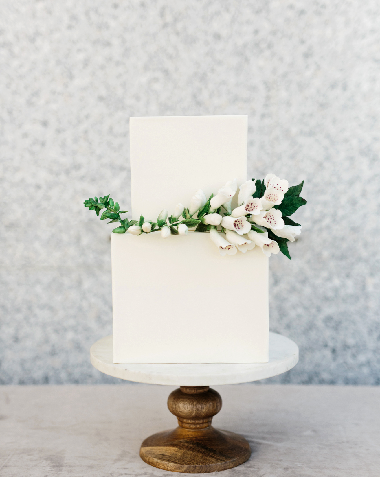 cubed wedding floral arrangement on simple white cake