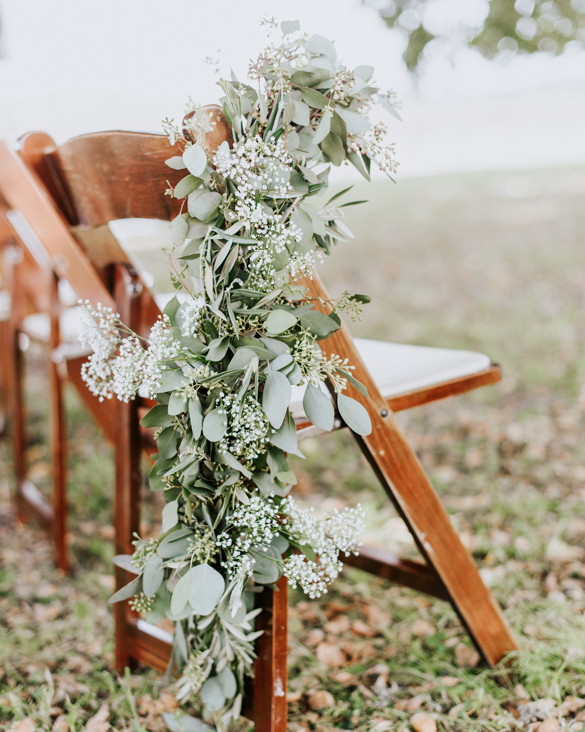 green eucalyptus with distressed wooden chairs outdoors