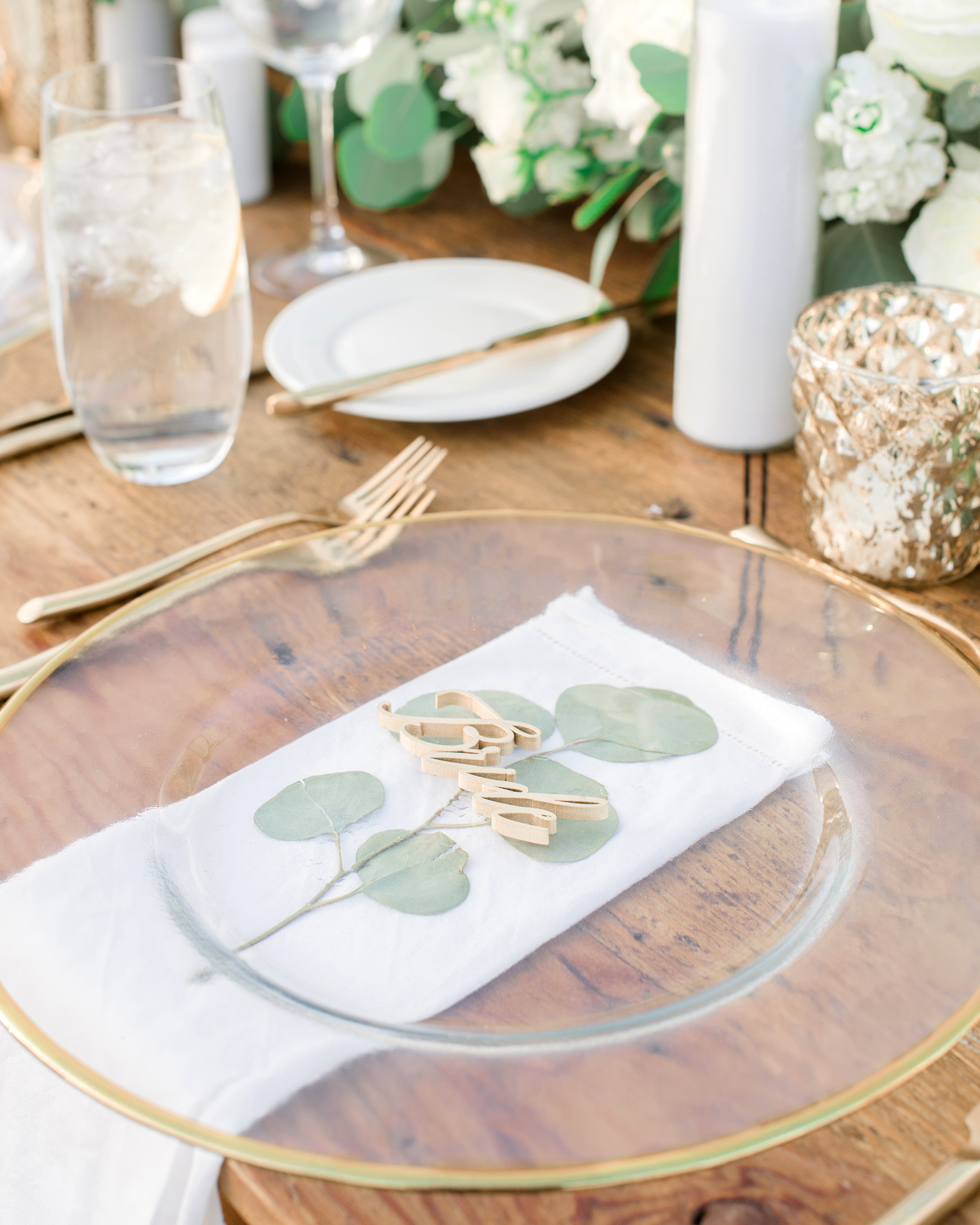 soft green eucalyptus under clear plates table setting