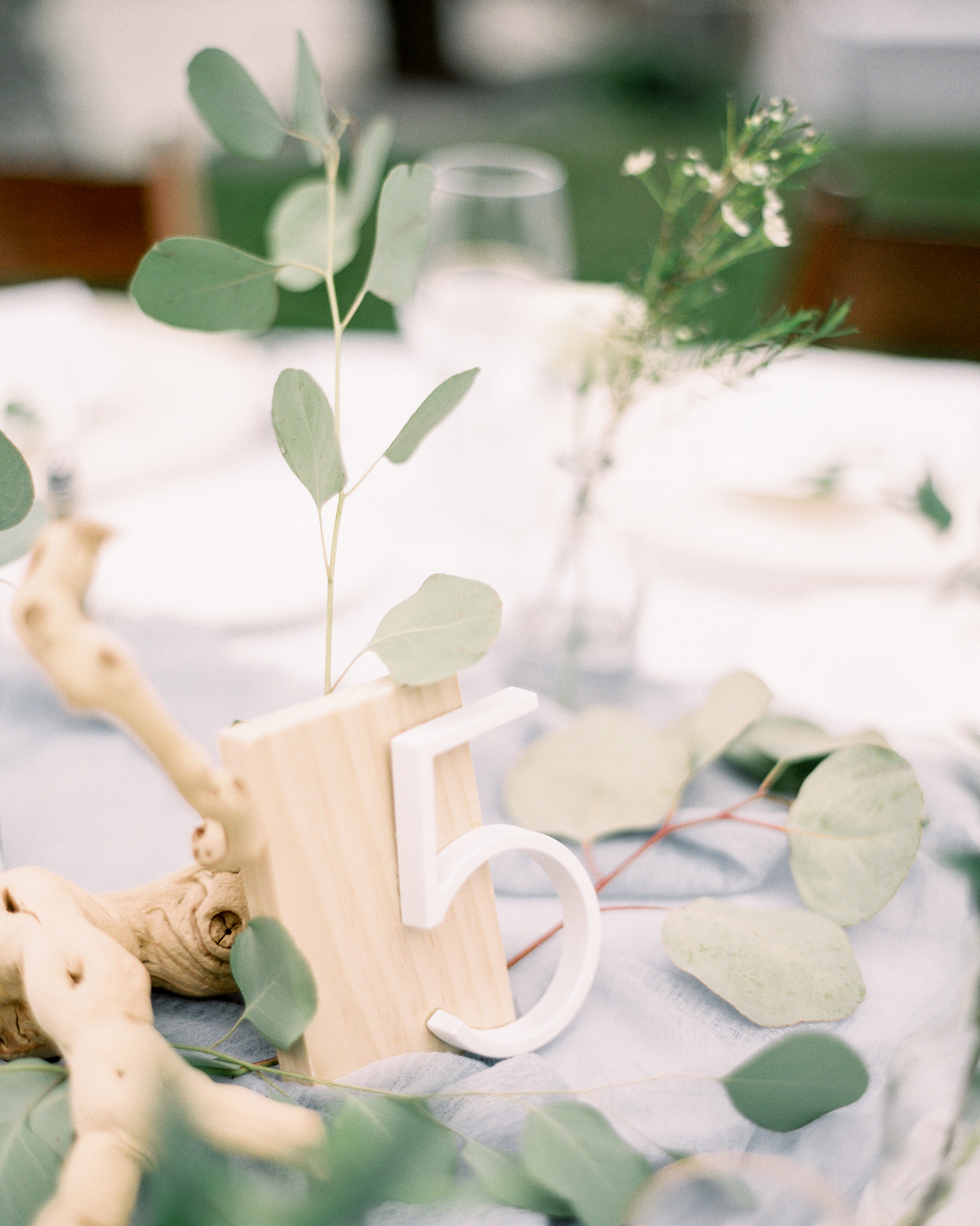 chic wooden table numbers eucalyptus tablescape