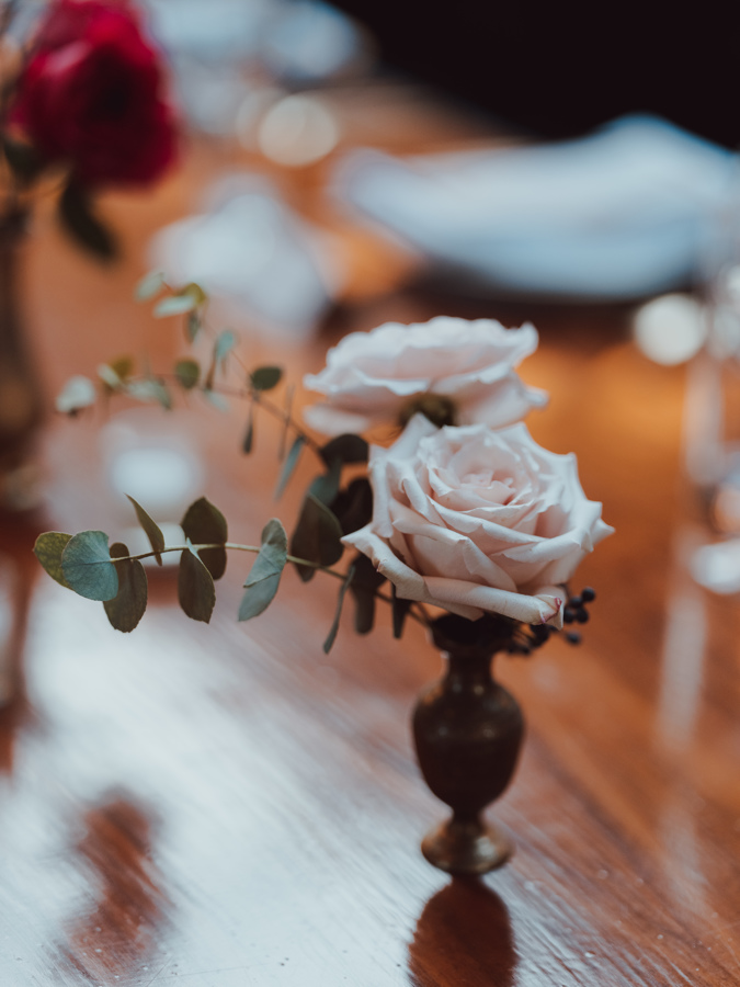 single rose buds in tiny vases table decor