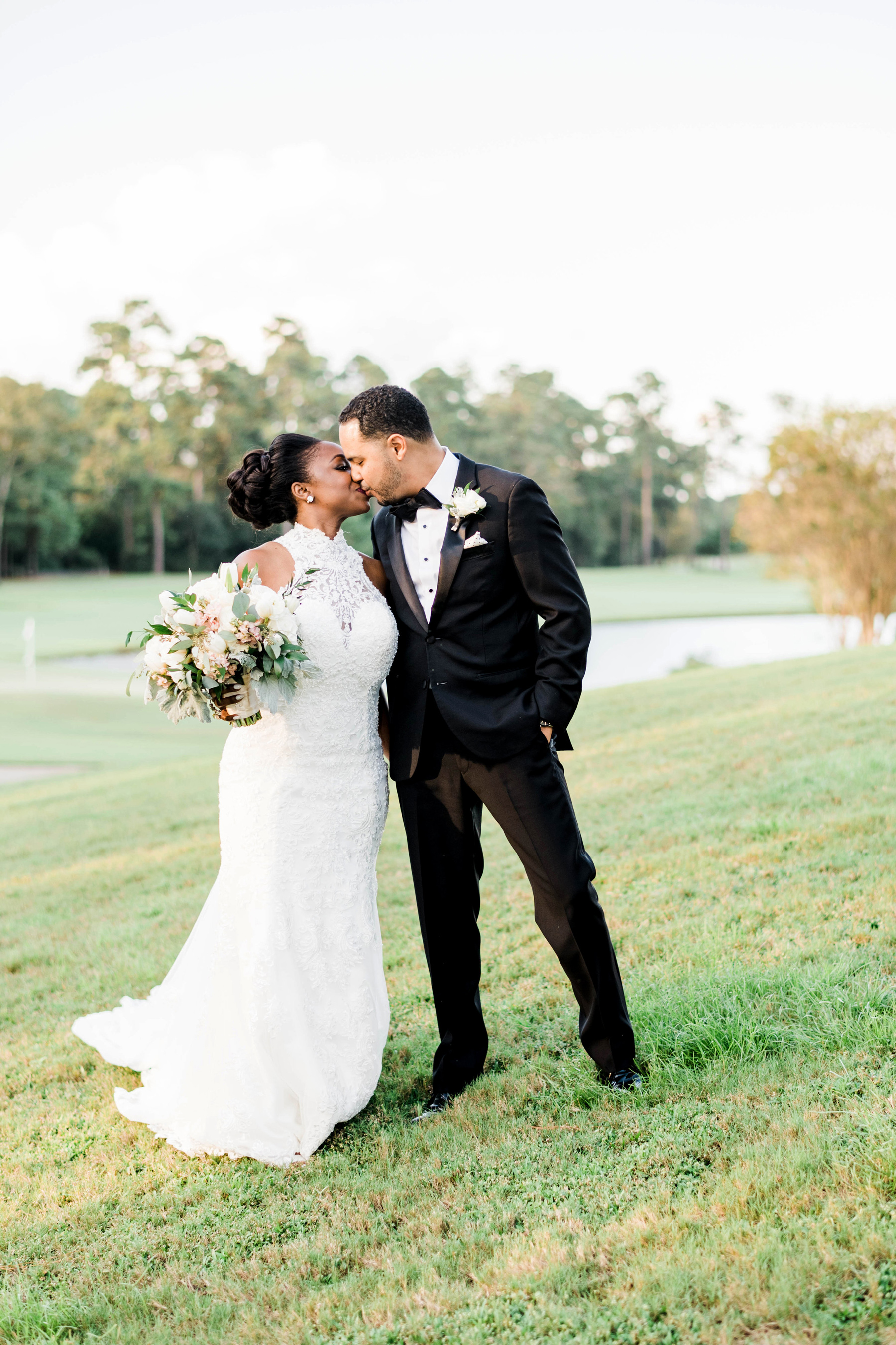 bride and groom share a kiss on a grassy lawn outdoors