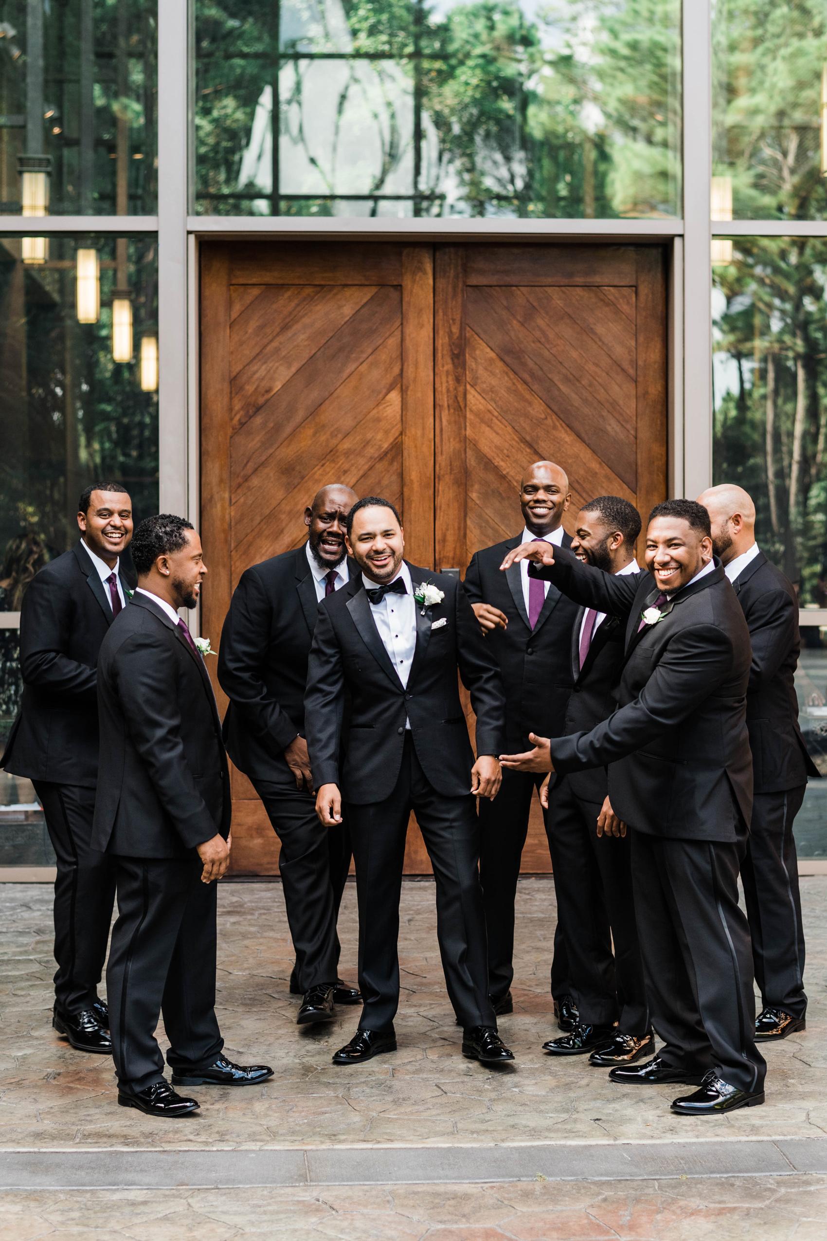 groom standing with groomsmen wearing black tuxedos