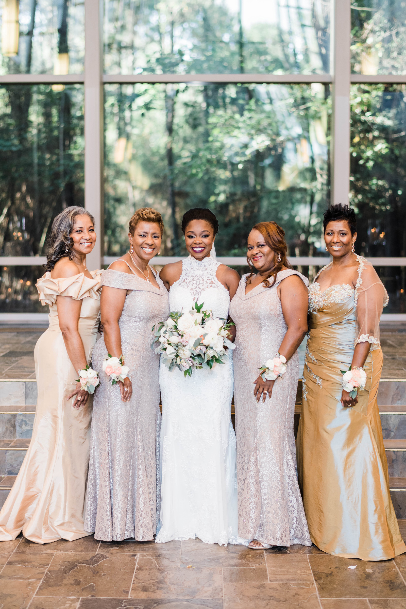 bride with four mothers-of-honor wearing gold and champagne colored floor length dresses
