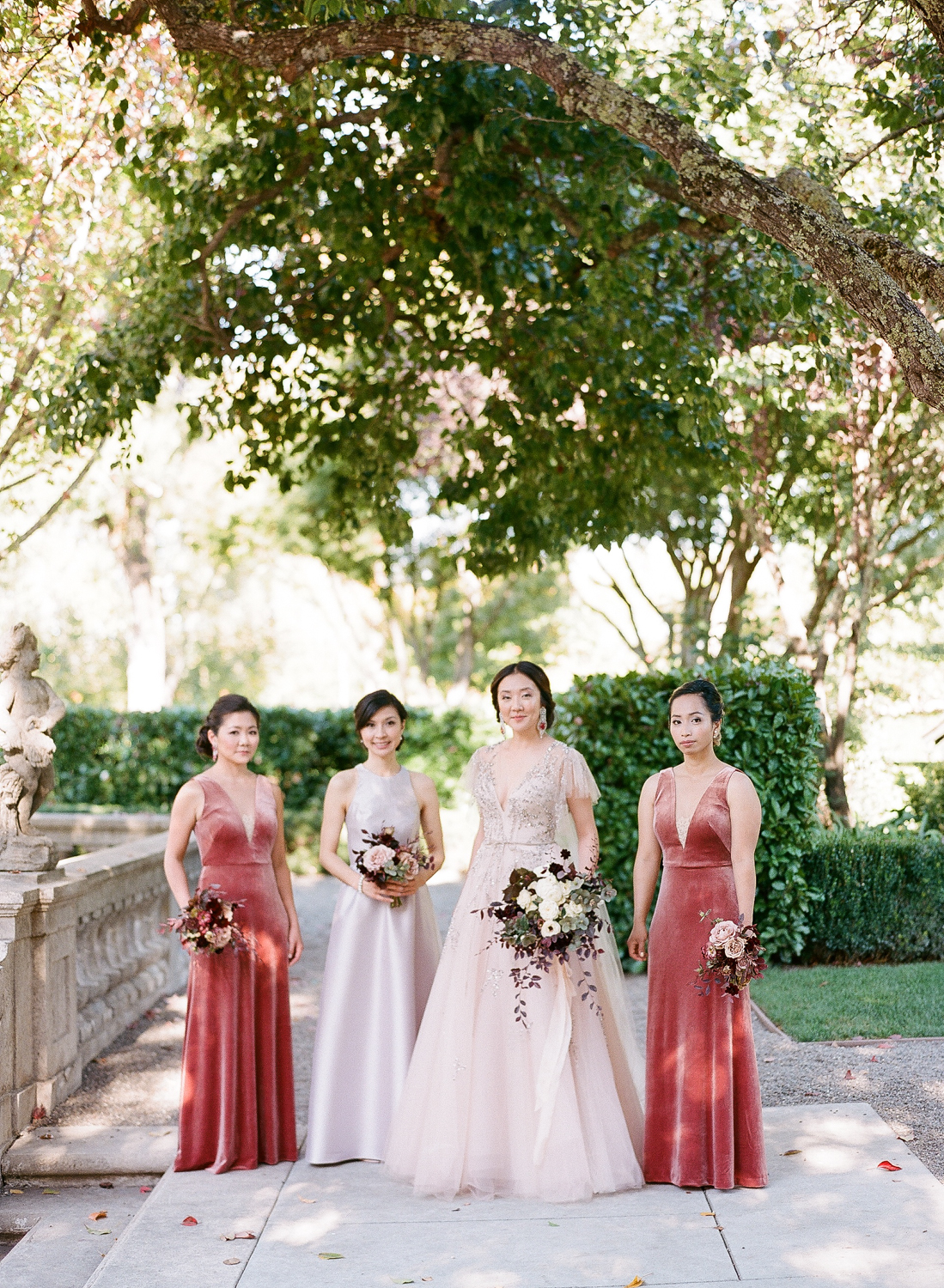 bride with maid of honor and bridesmaids wearing blush pink to red shade dresses