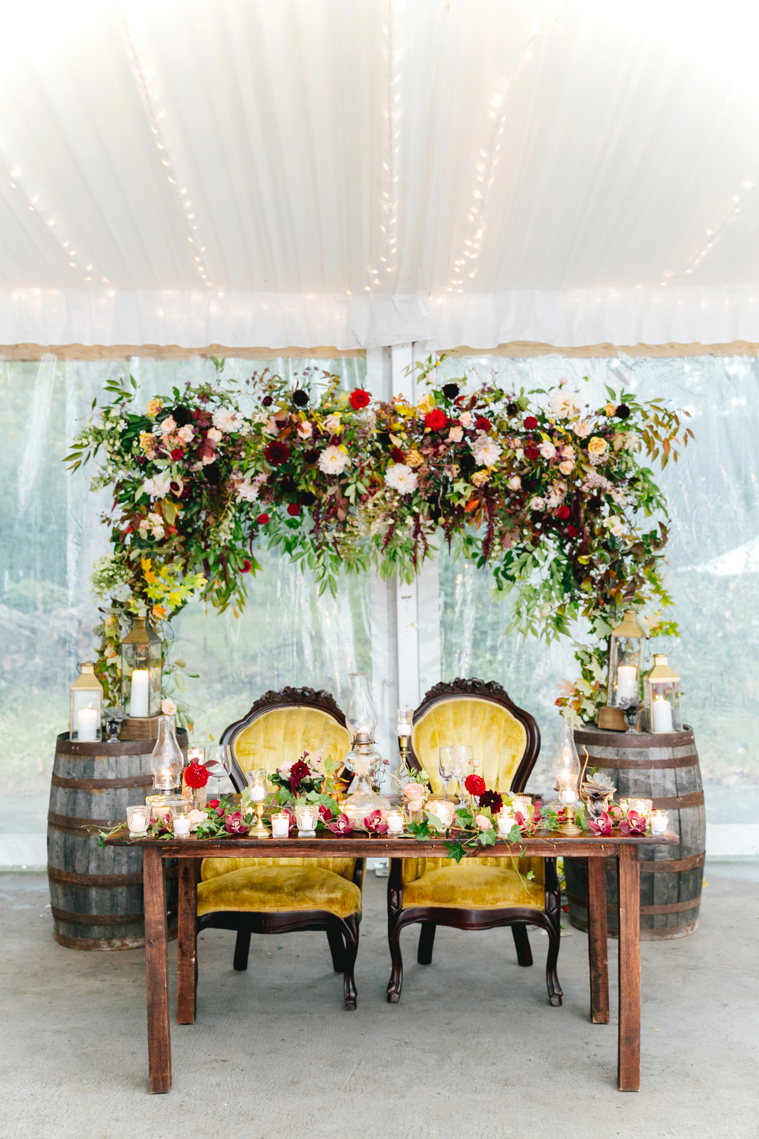 sweetheart table floral arch yellow chairs and barrels