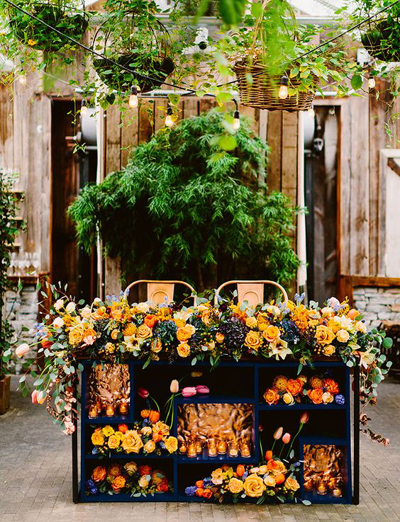 sweetheart table outdoor bookcase with orange flower arrangements