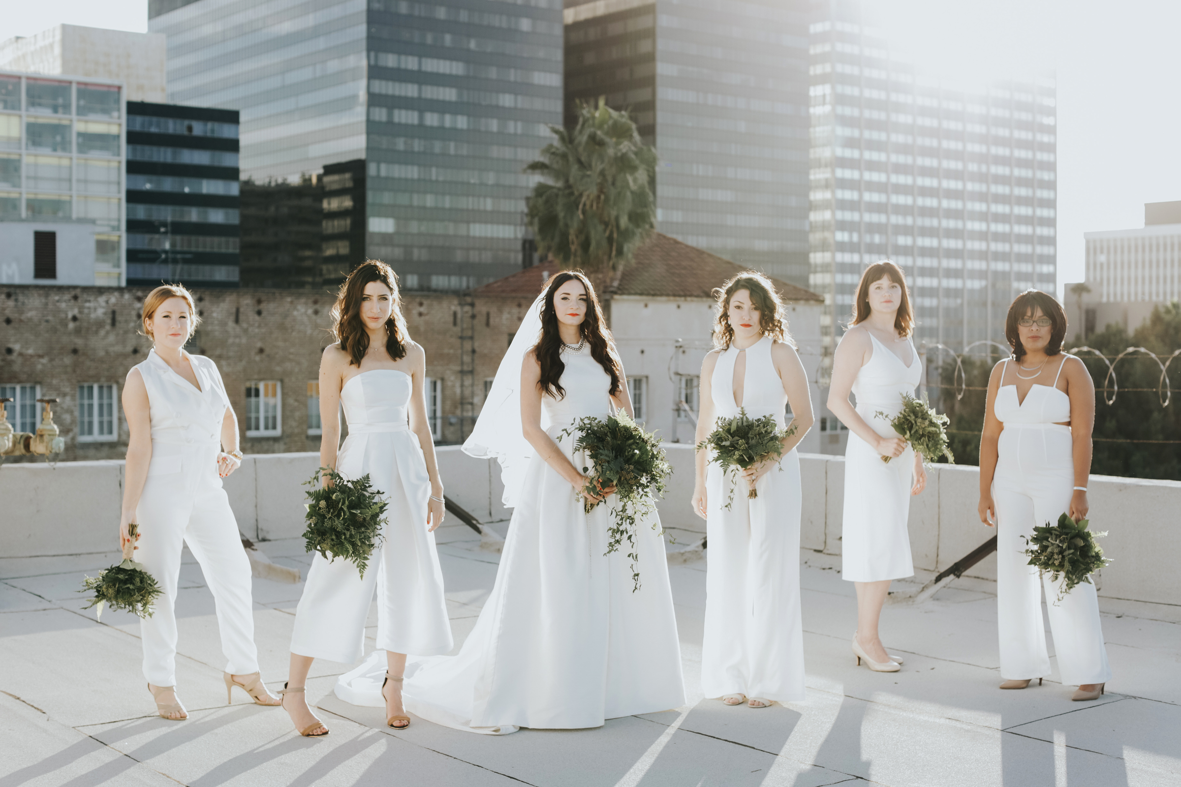 women posing on roof wearing white bridesmaids jumpsuits