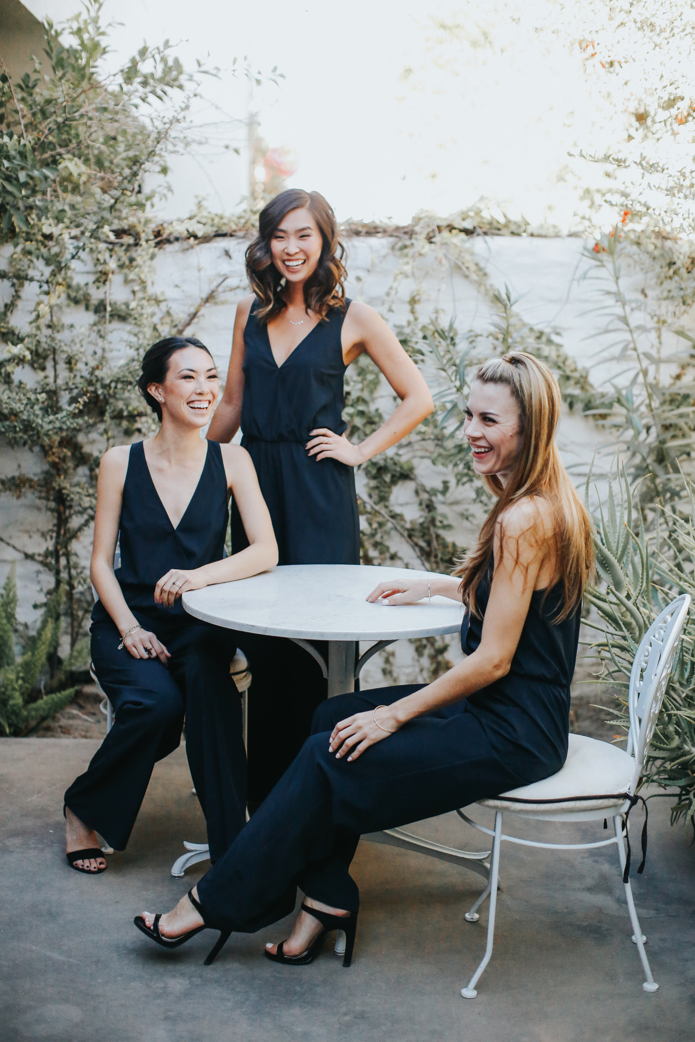 women sitting at round table wearing bridesmaids jumpsuits