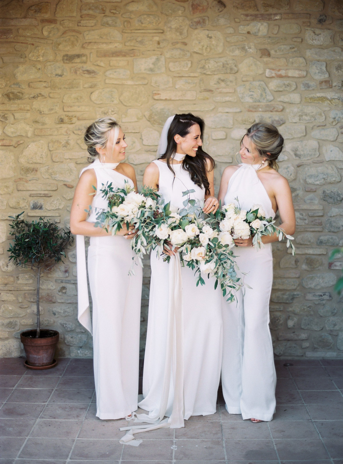 women wearing white high neckline bridesmaids jumpsuits