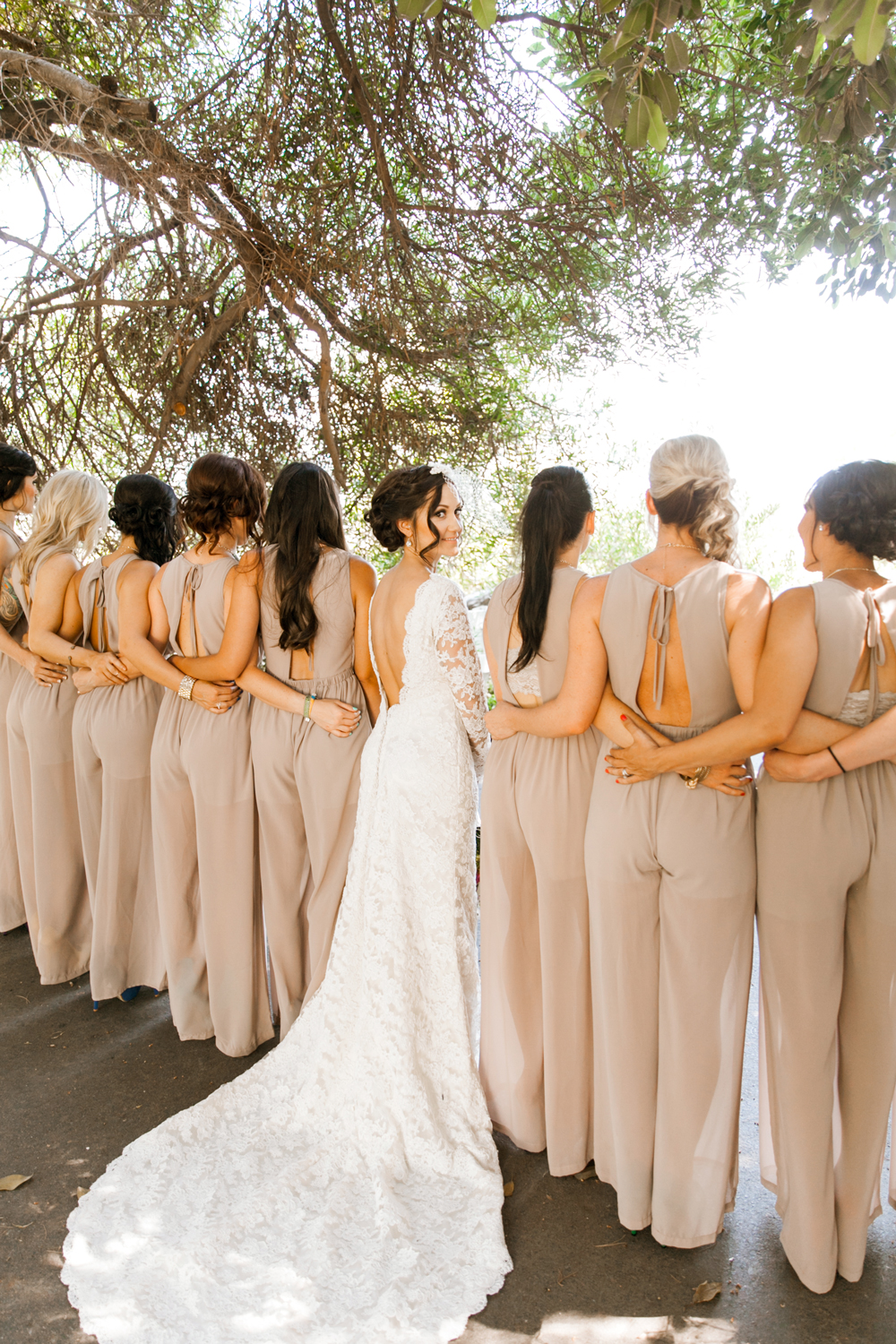 the backs of women wearing bridesmaids jumpsuits