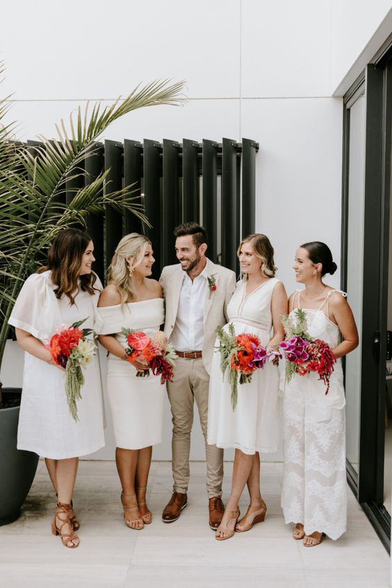 women standing with groom wearing mismatched white bridesmaids dresses and jumpsuit