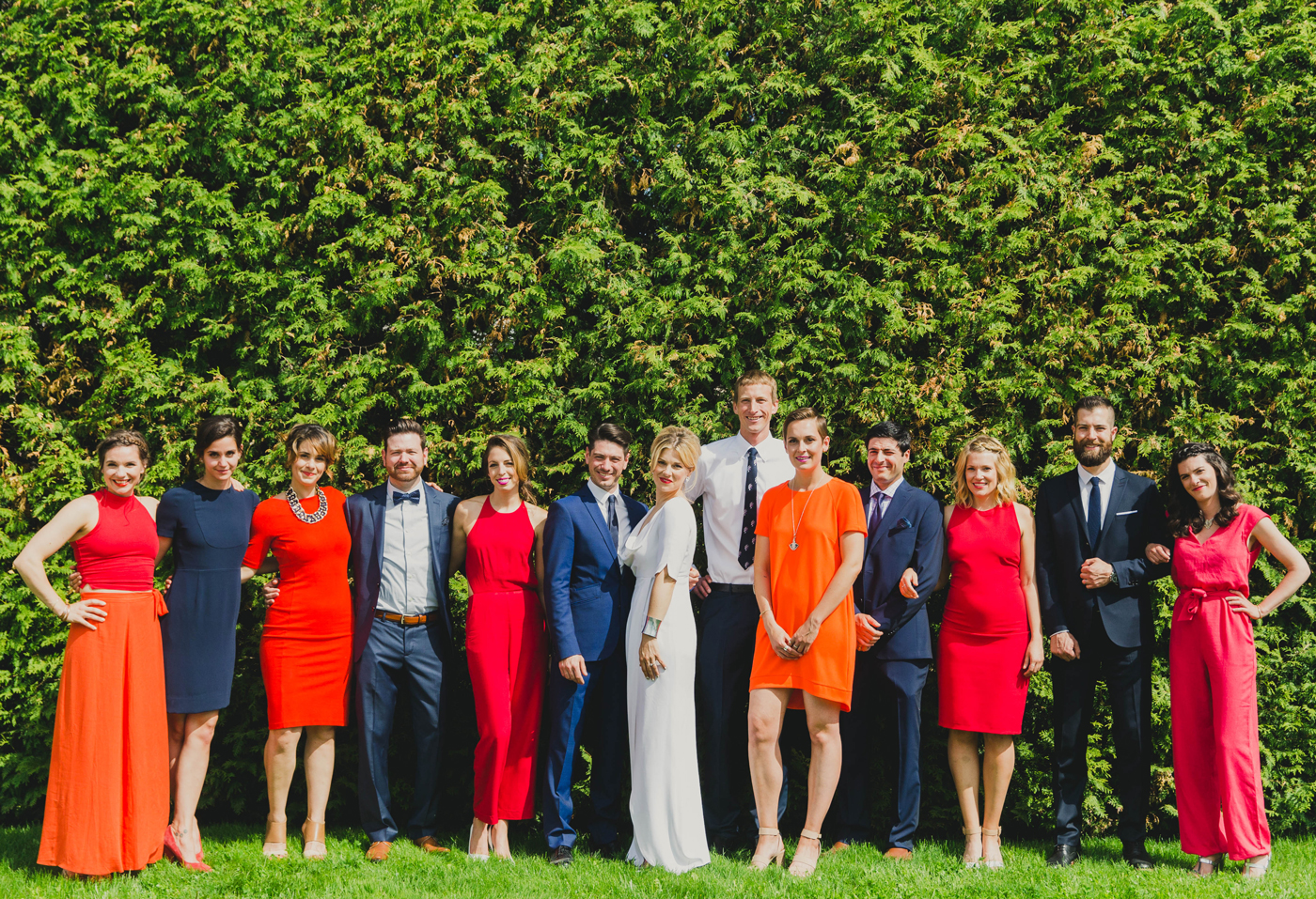 wedding party standing in front of hedges featuring women wearing mismatched bridesmaids jumpsuits