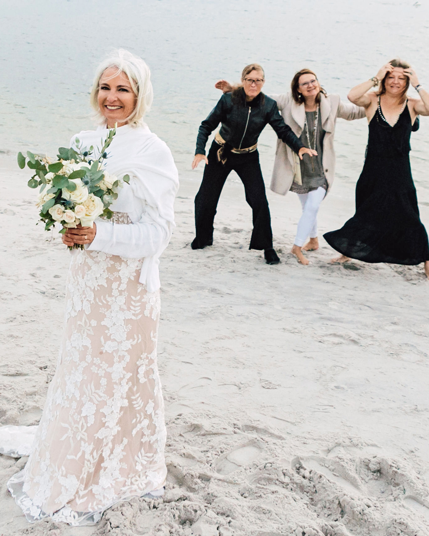 bridal party bouquet toss on beach