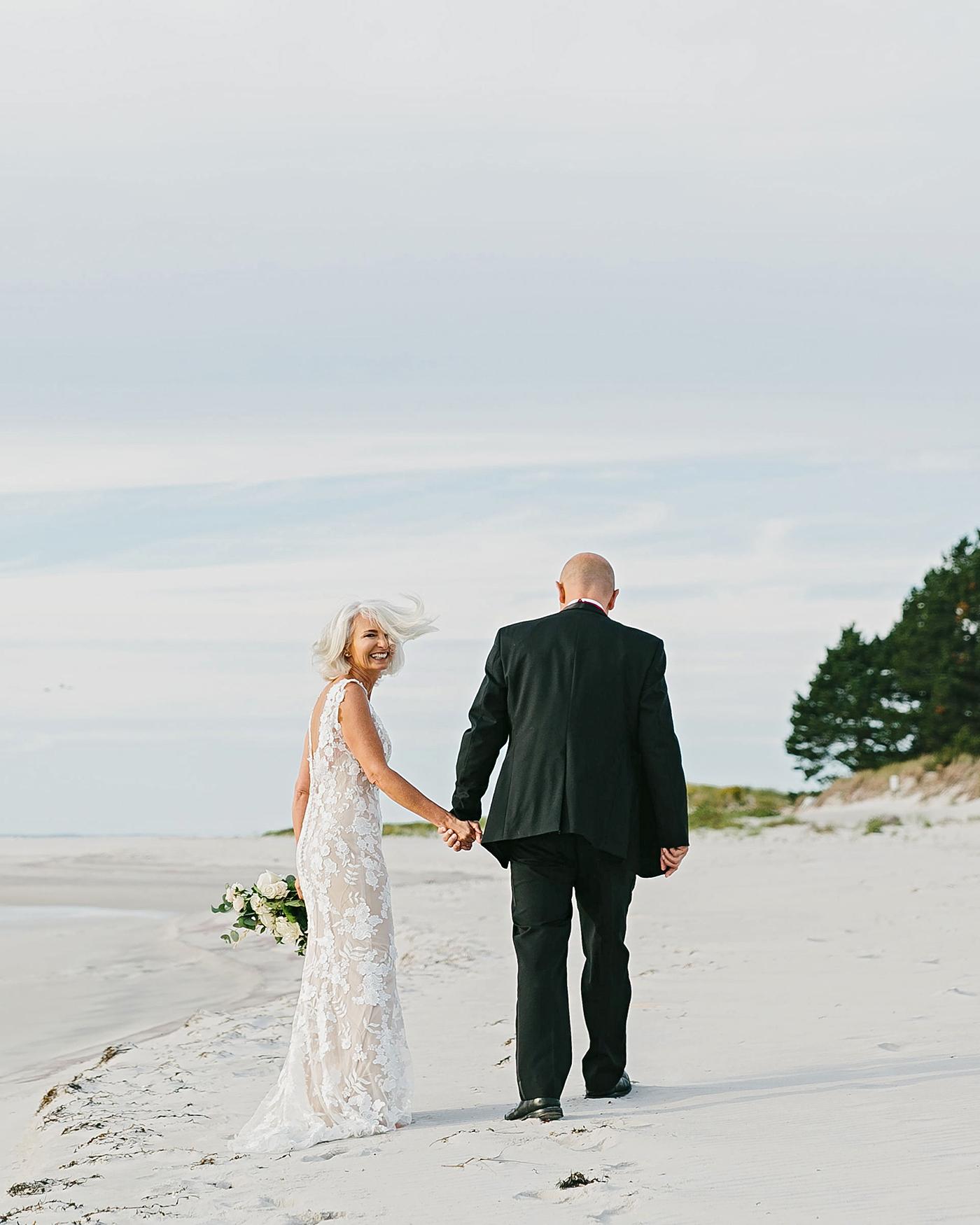 bride and groom walking away on beach