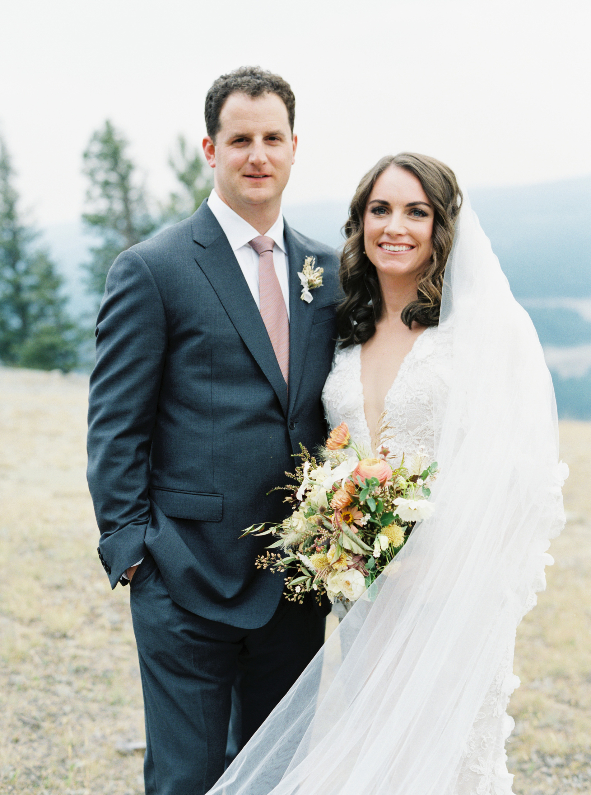 bride and groom stand outside on hillside for wedding portraits