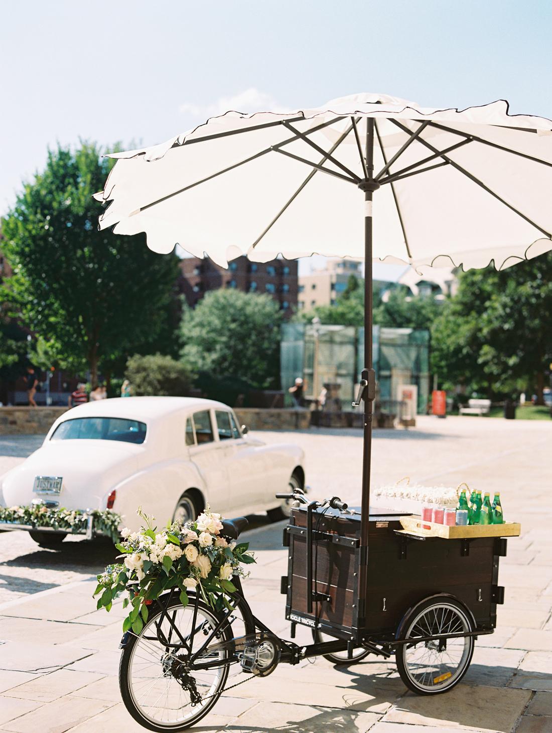 rose bicycle cart with white umbrella next to white vintage car