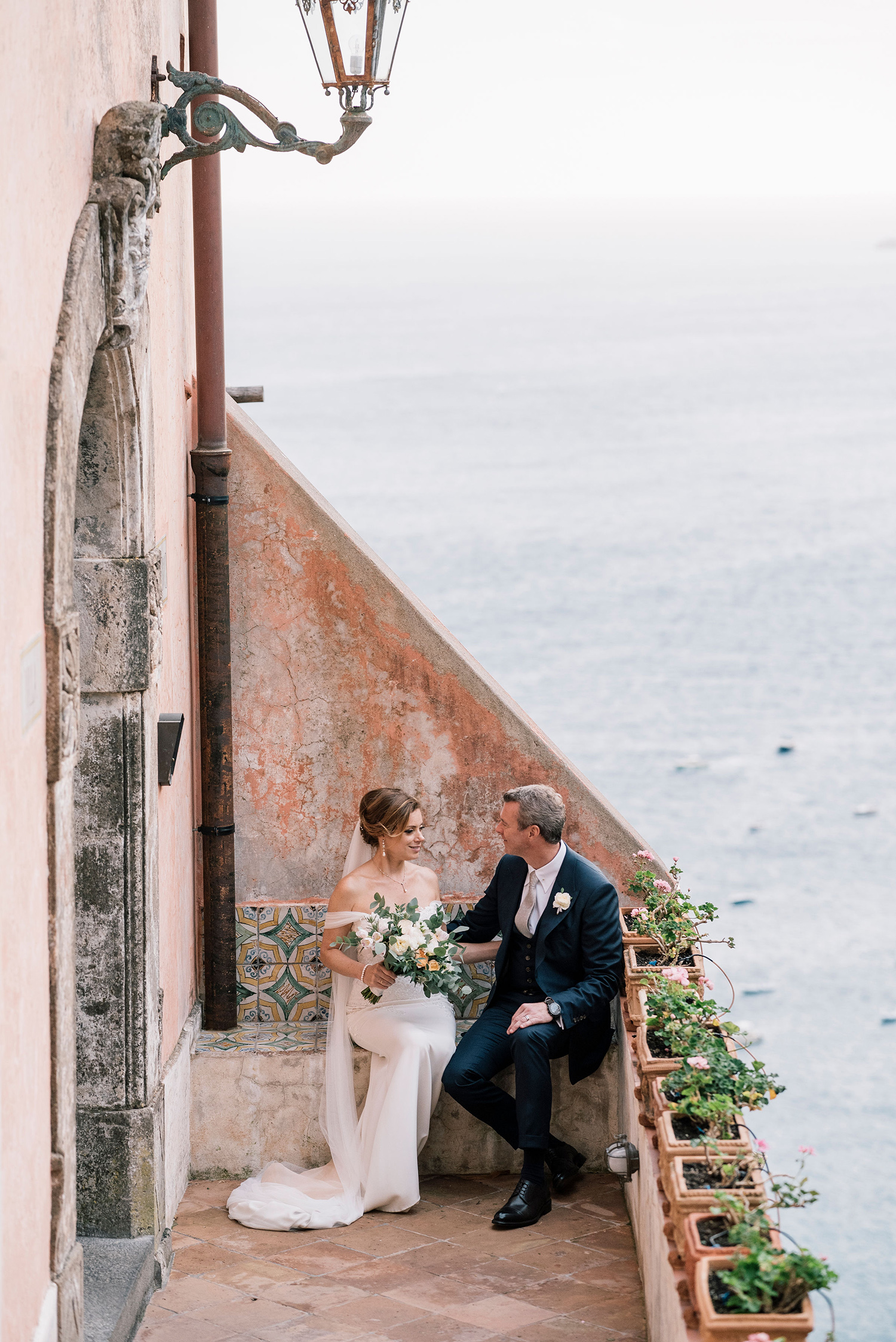 cara david wedding couple sitting on steps above coast