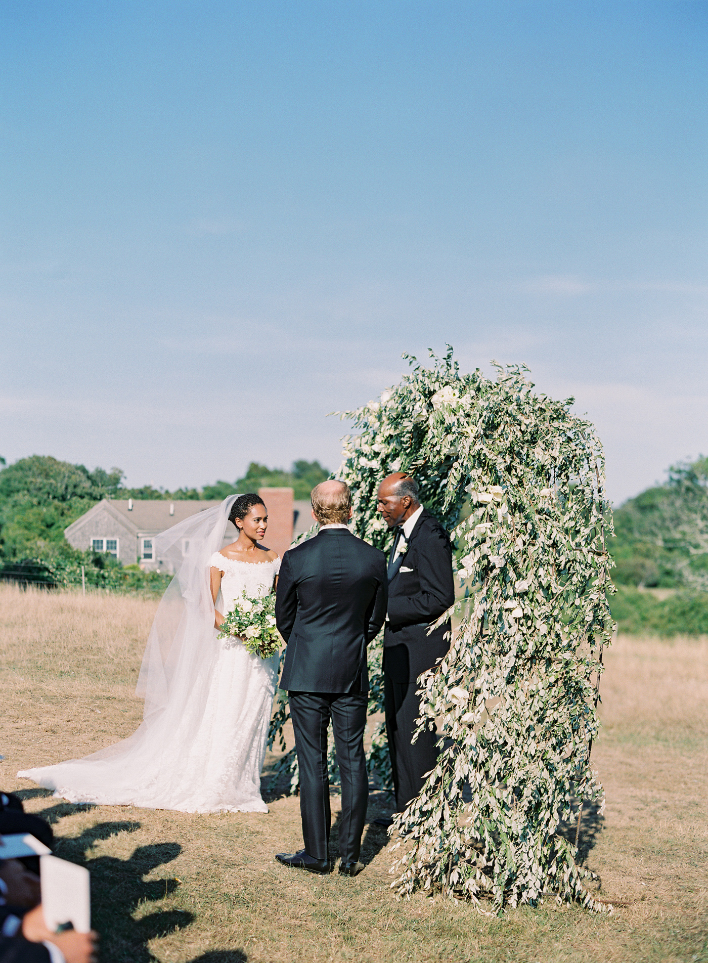 bride and groom next to floral arch outside during wedding ceremony