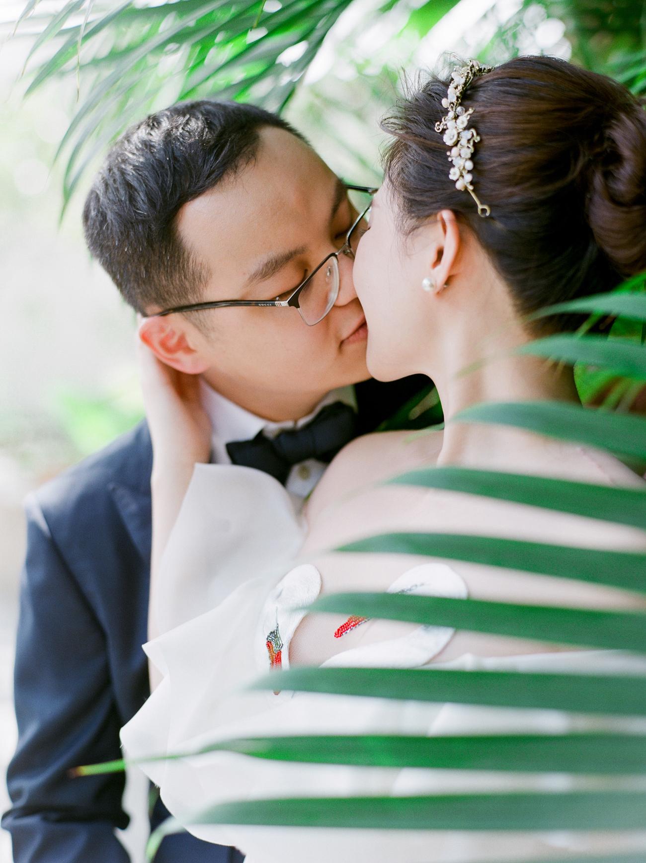 groom kisses bride under large tropical leaves