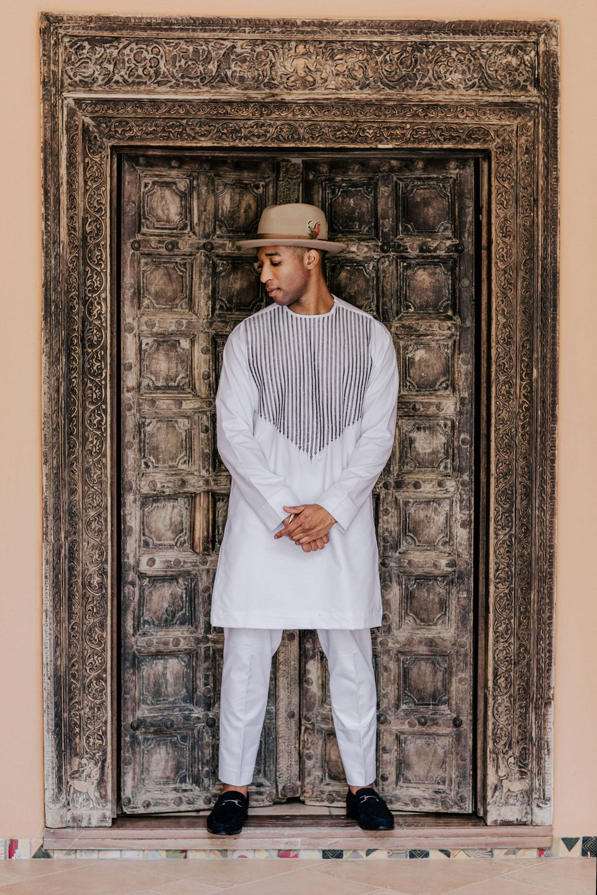 Groom wearing Malian heritage white African Dashiki shirt and pants set