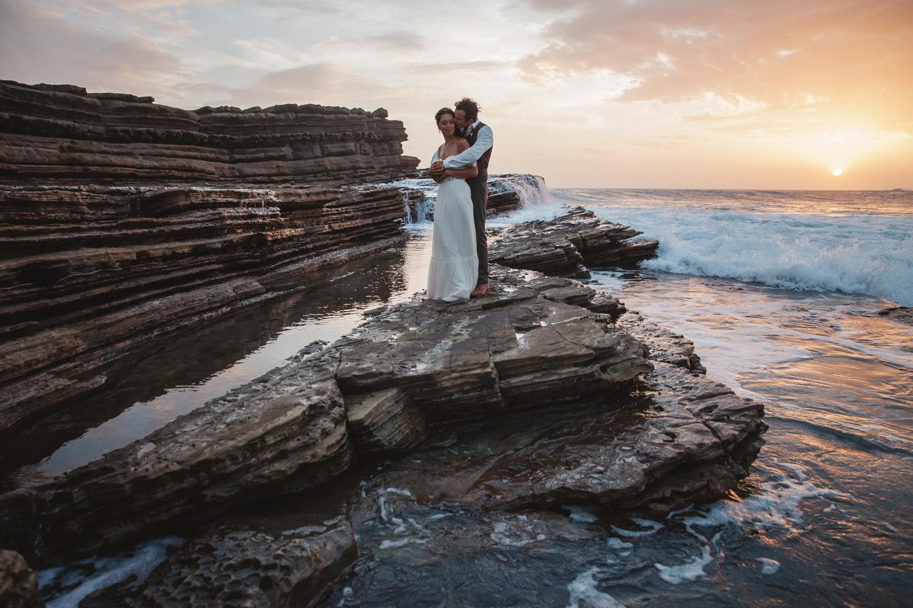 sunset wedding photos bride and groom embracing on oceanic rock
