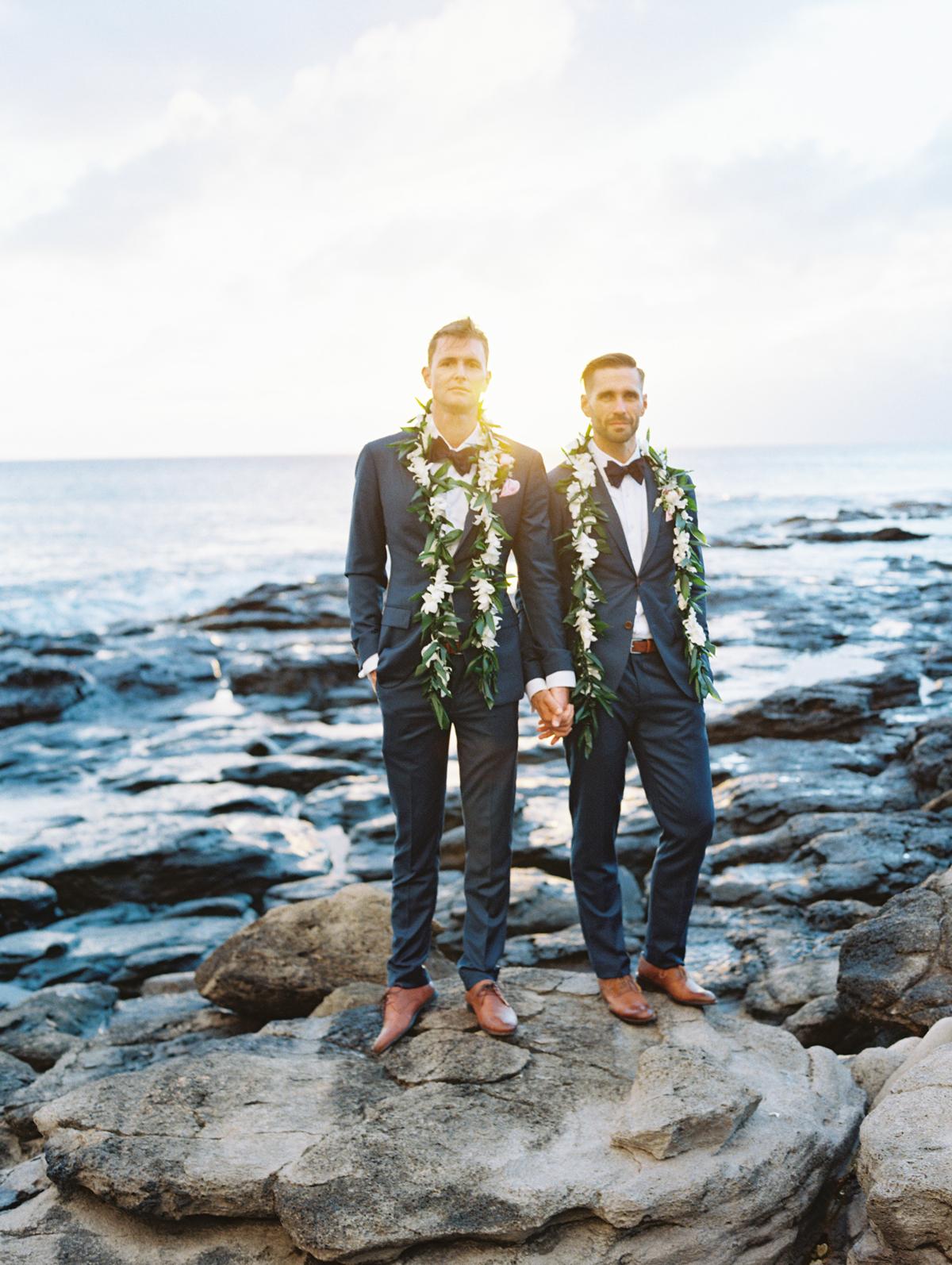 sunset wedding photos grooms holding hands on oceanic rock