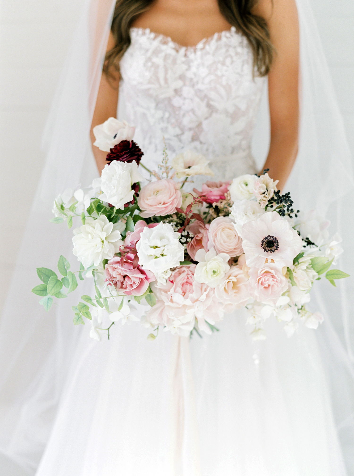 four varieties of roses with anemones, ranunculus, and lisianthus bridal bouquet