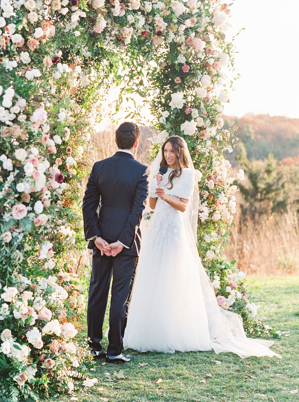 bride and groom under floral arch during mountain top wedding ceremony