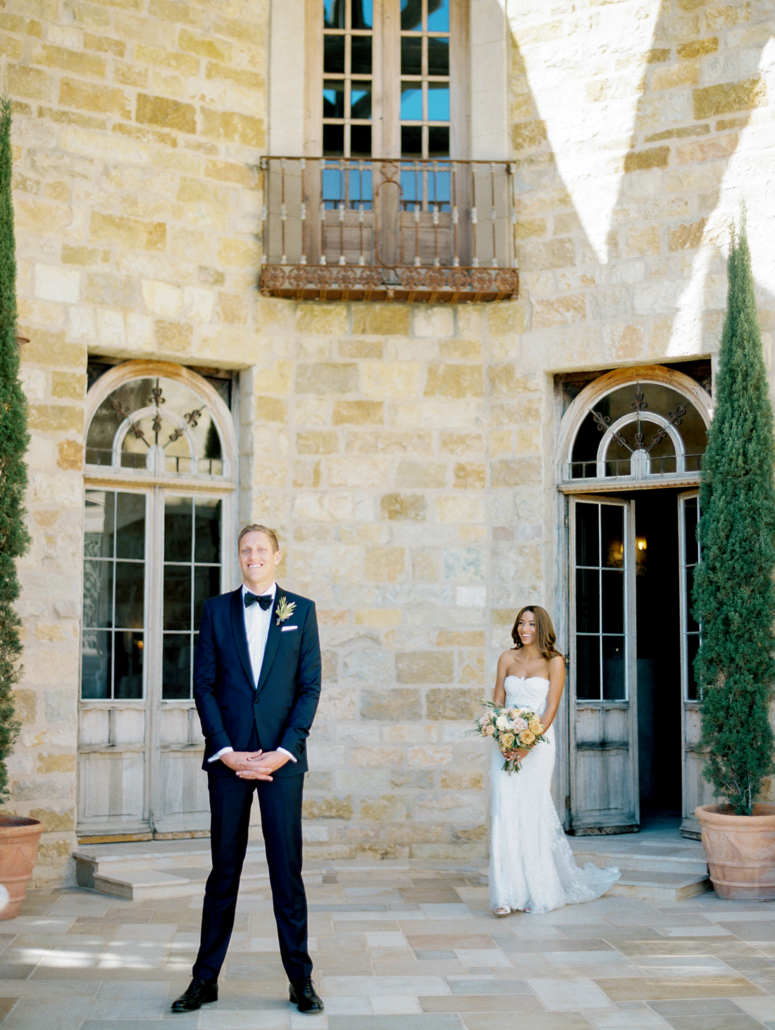 bride standing behind groom before first look