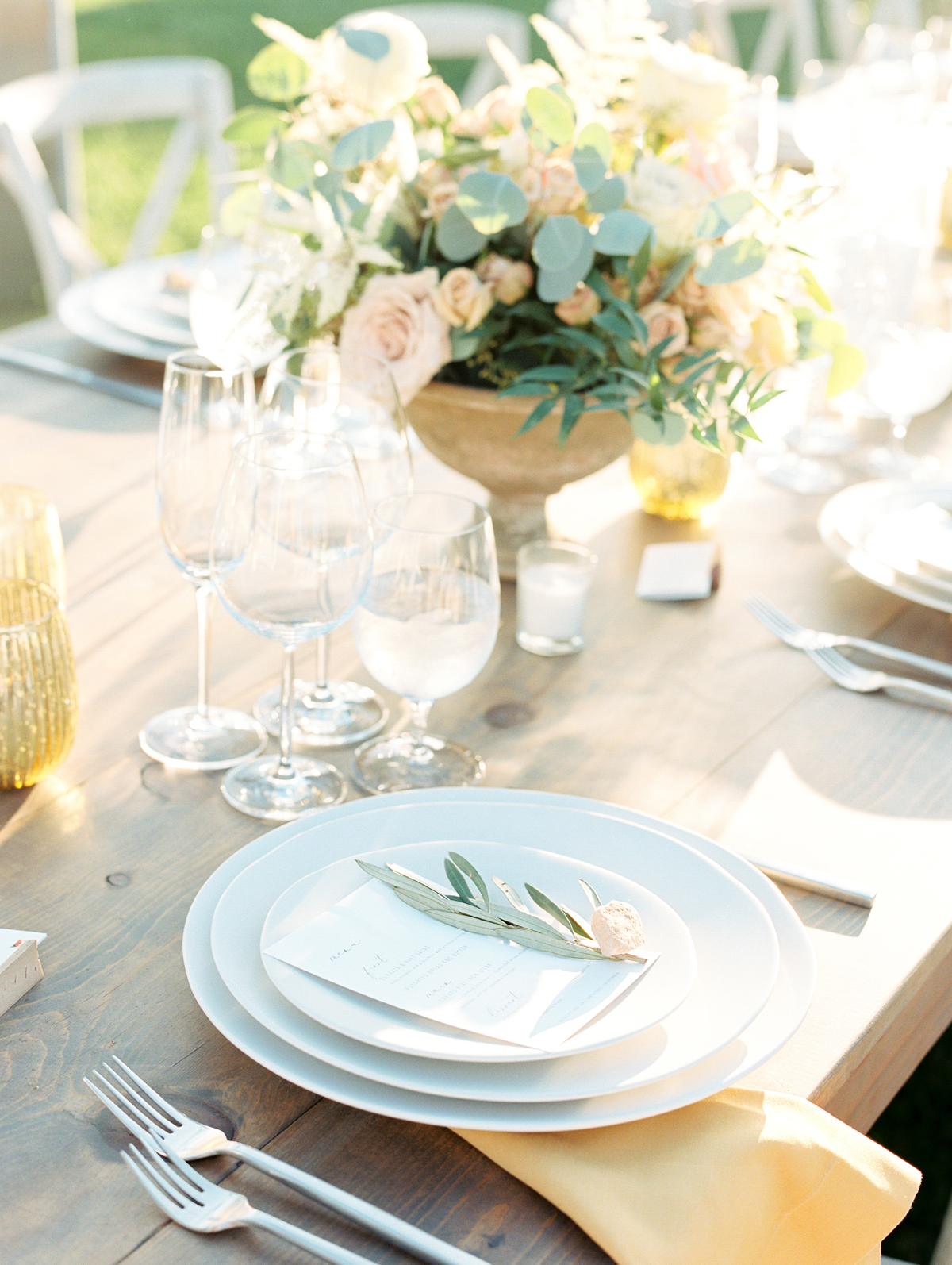 low floral centerpieces on long wooden tables