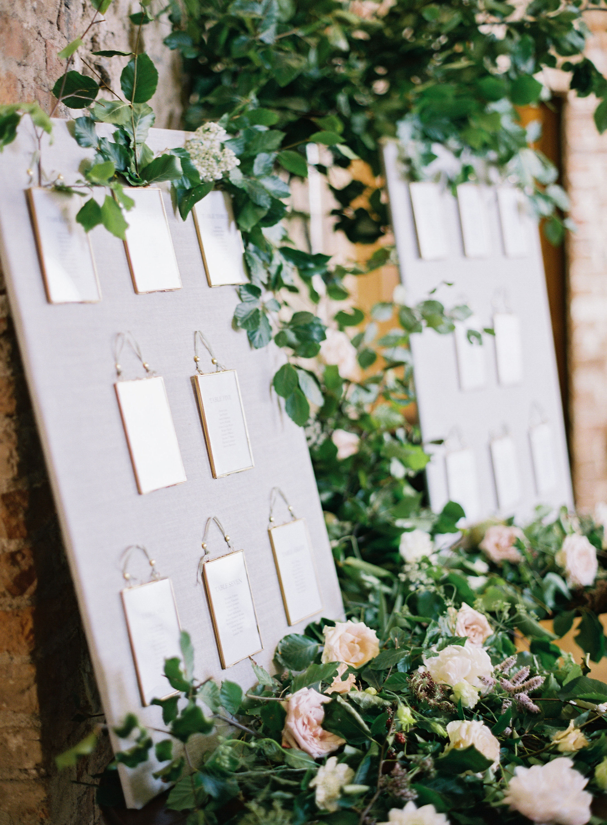 escort cards pinned to greenery and floral covered boards