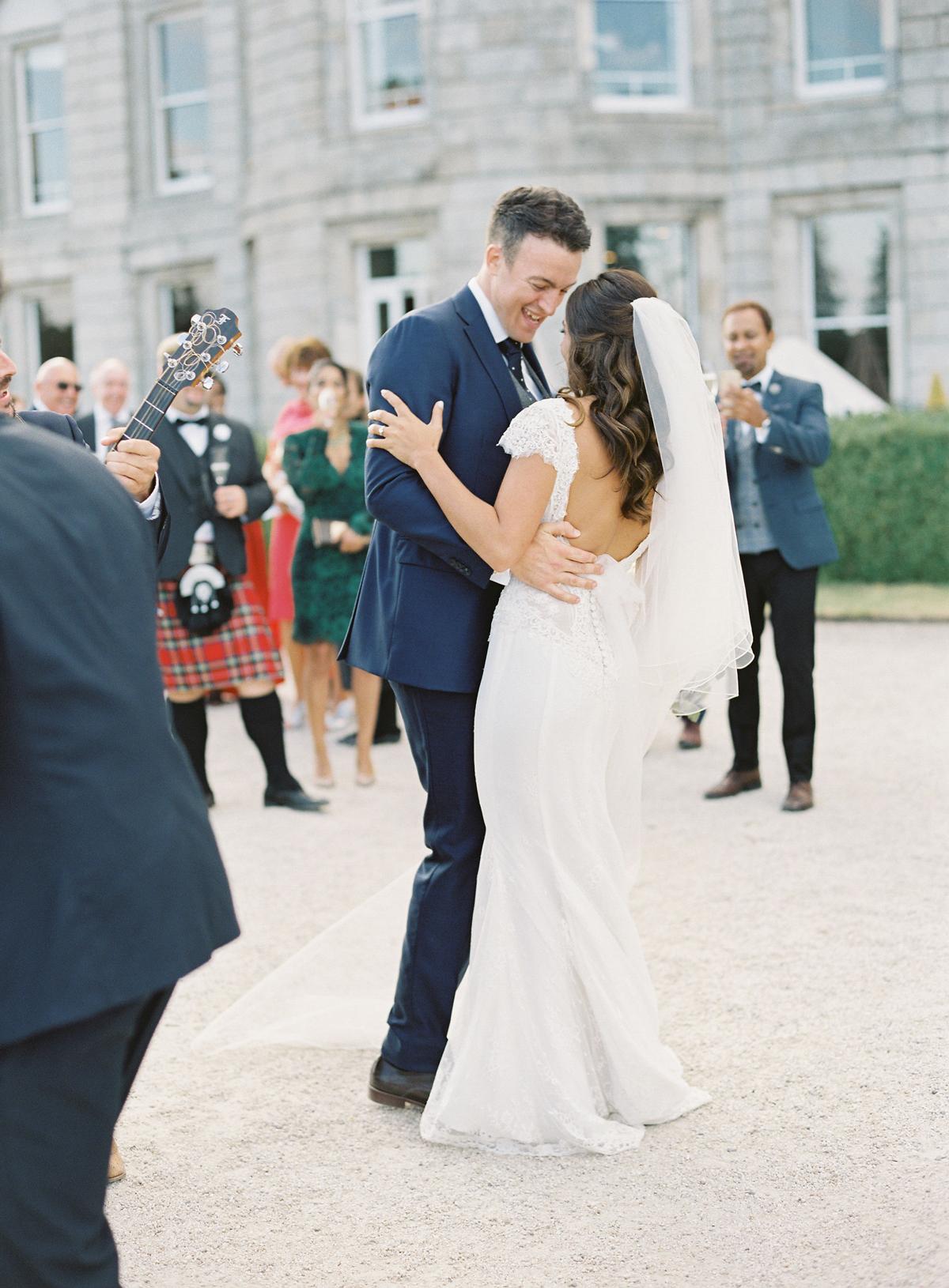 bride and groom dancing outside wedding venue