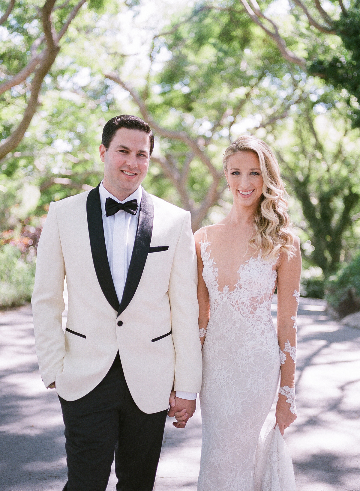 bride and groom holding hands outside for portrait