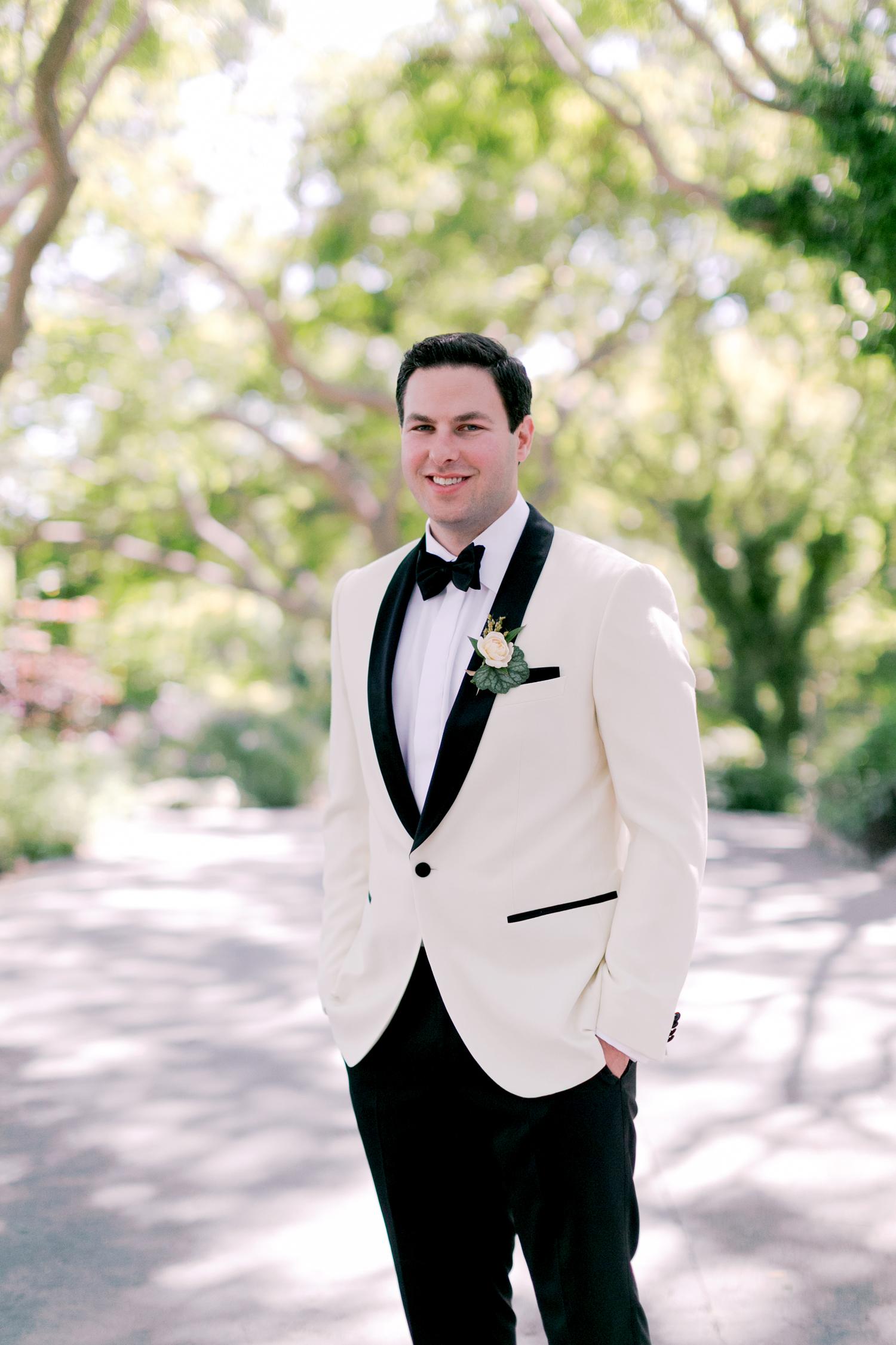 off white jacket black tuxedo pant groom wedding outfit
