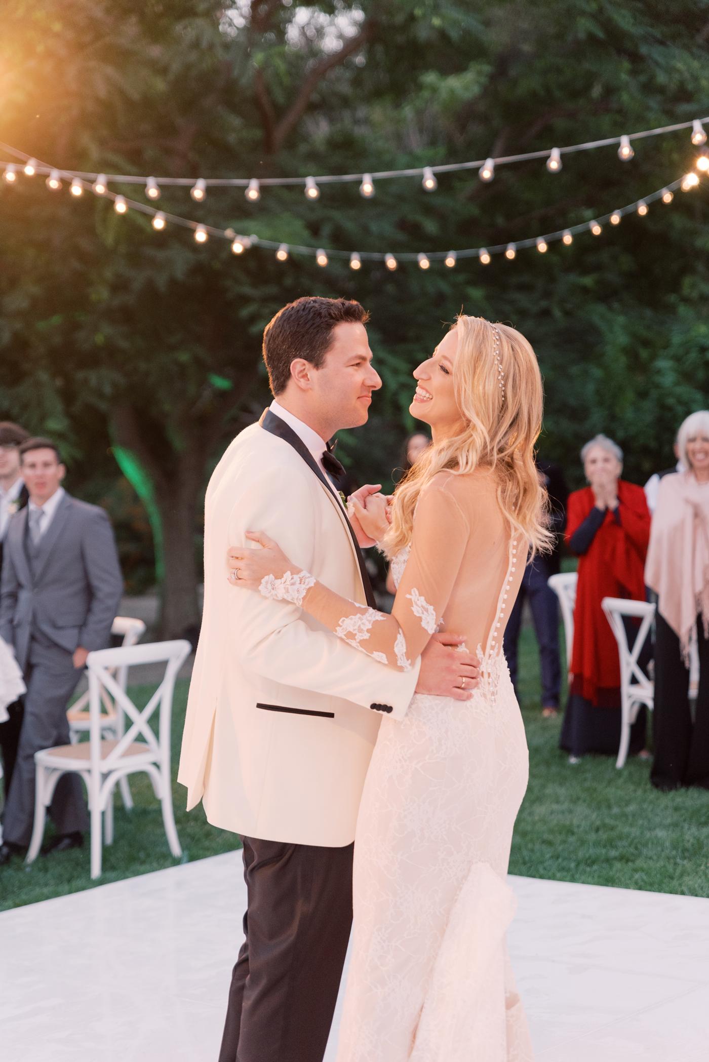 bride and groom first dance outside dance floor string lights