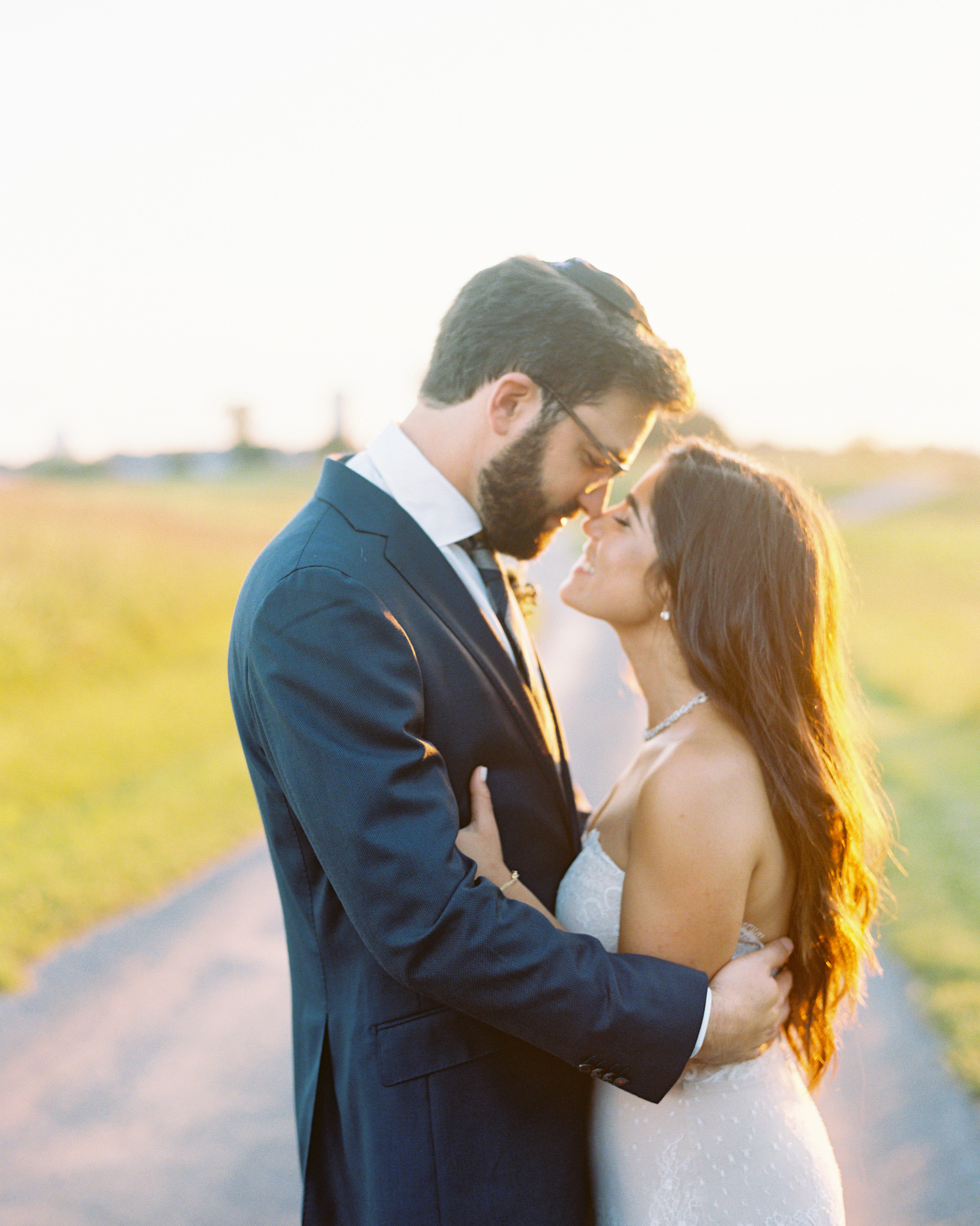 loving couple pose outdoors in sunlight