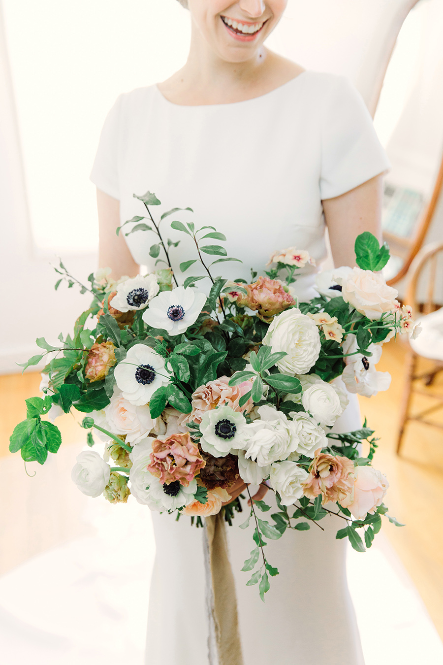 cream, pink, and peach anemones, roses, and other blooms floral bouquet
